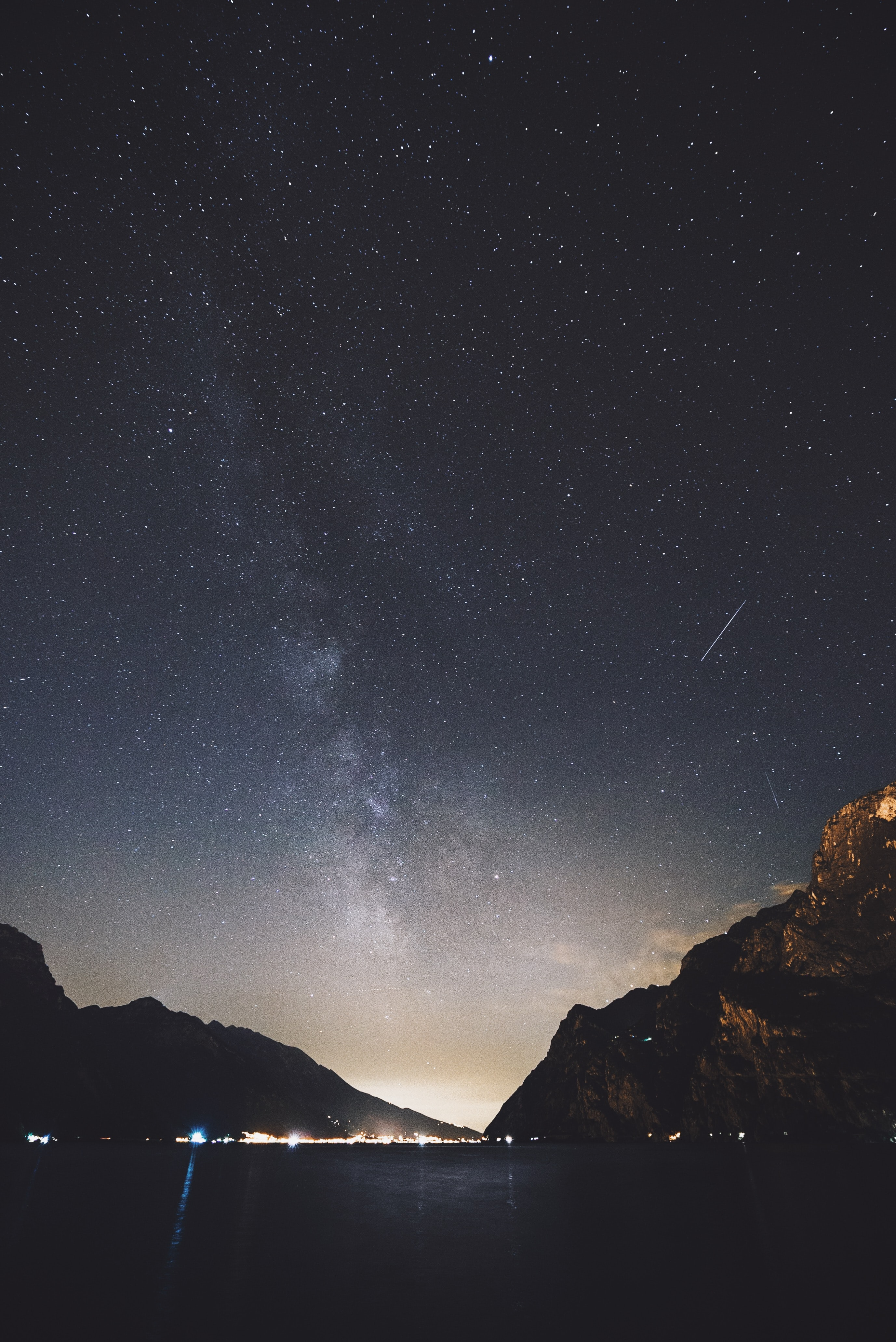 The milky way and a shooting star over the lake and mountain at Riva del Garda