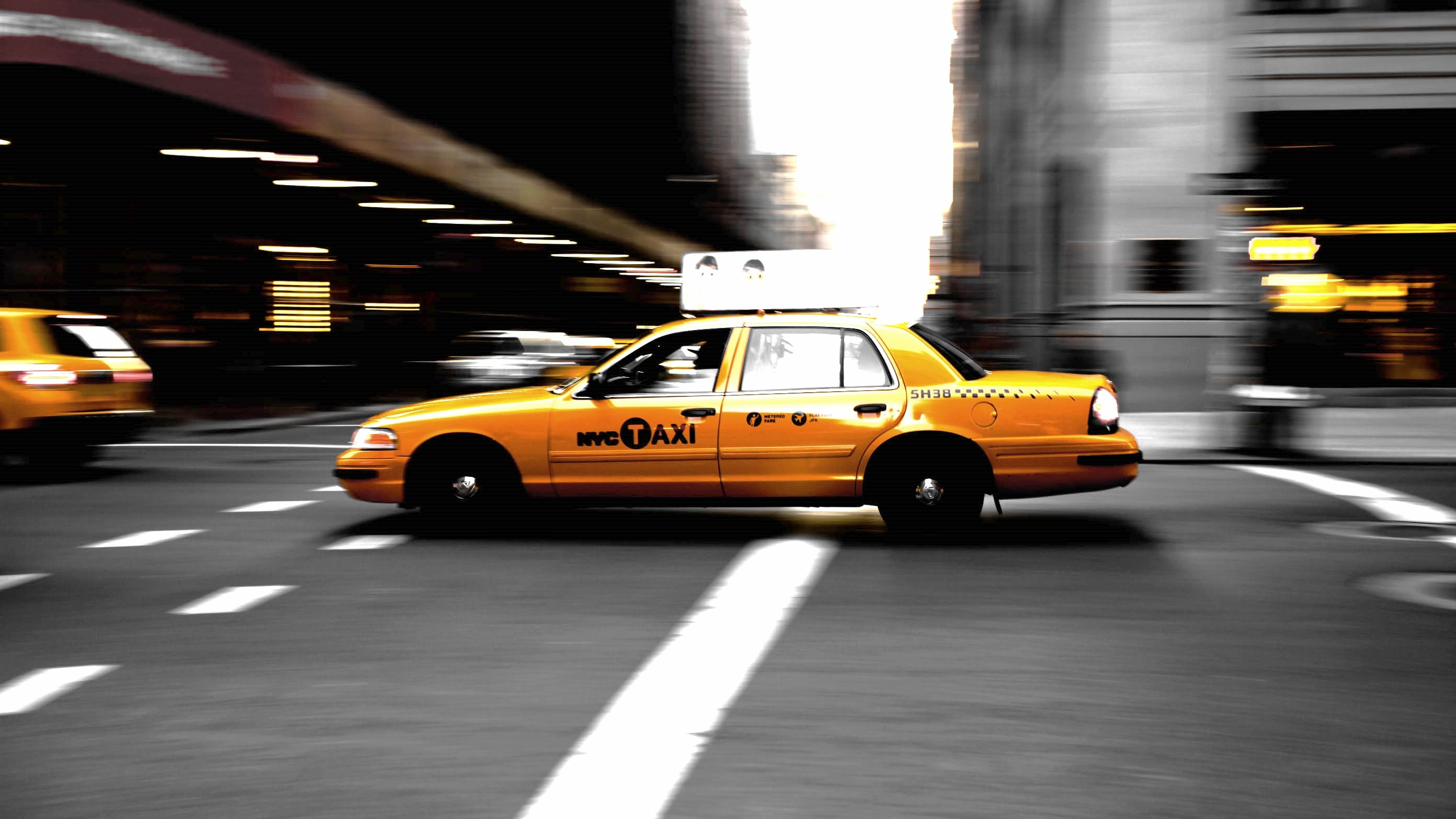 panning photography of yellow taxi on road