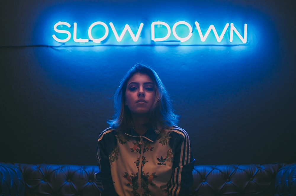 woman sitting on brown sofa under slow down neon signage