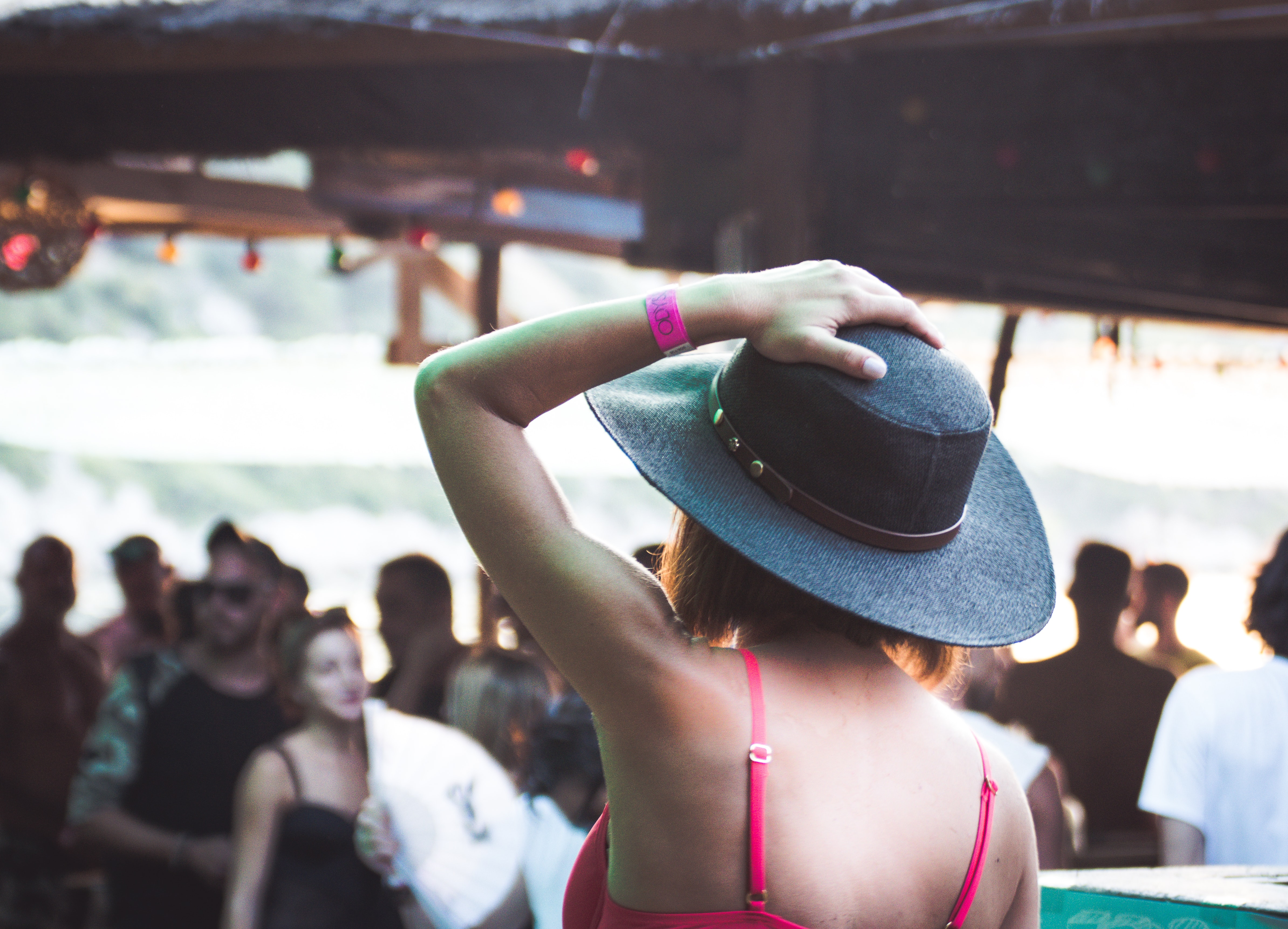 A woman is holding her hat and facing the crowd at Cariocas Beach Bar