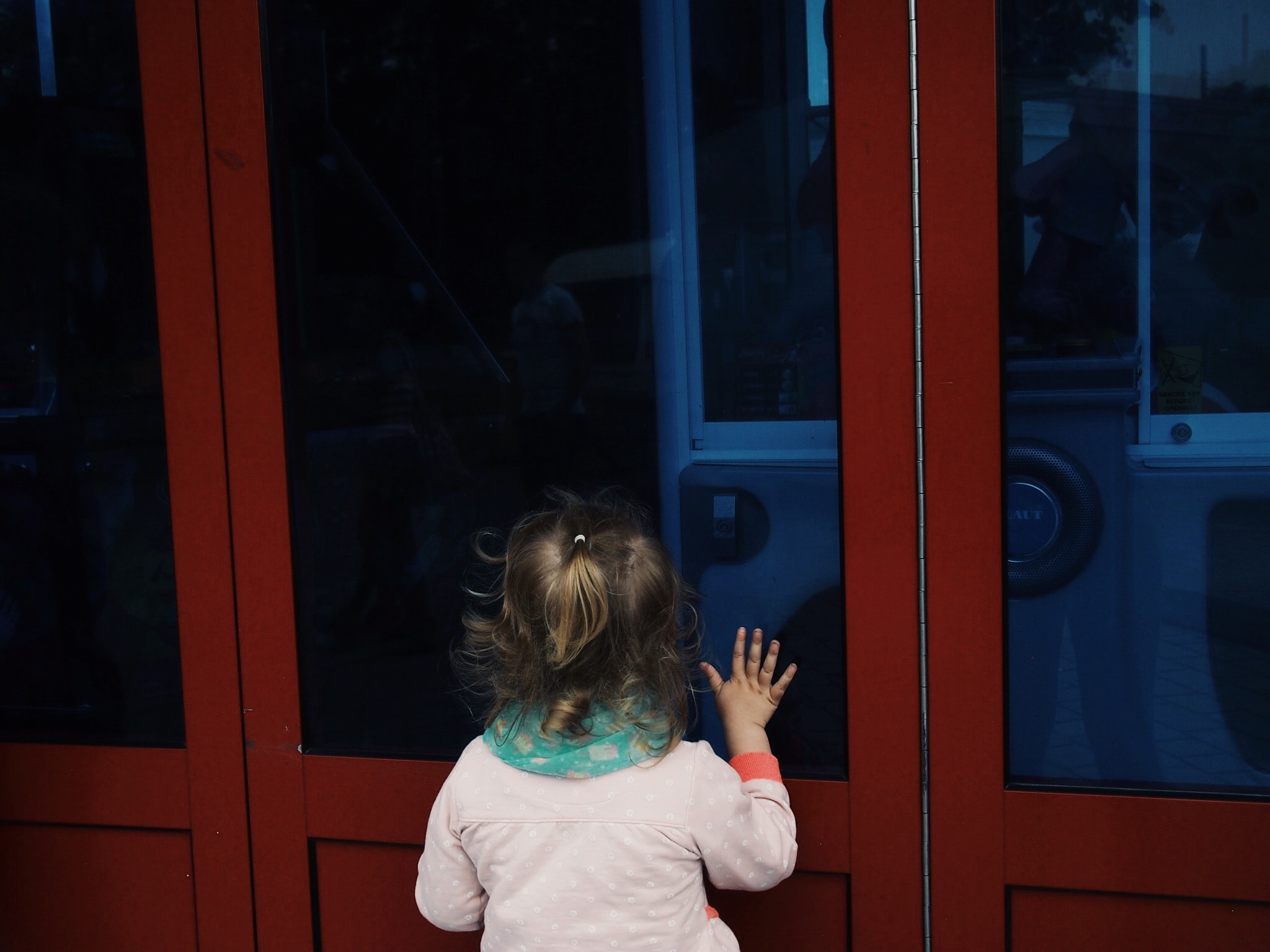 back of toddler girl looking through closed black glass wall