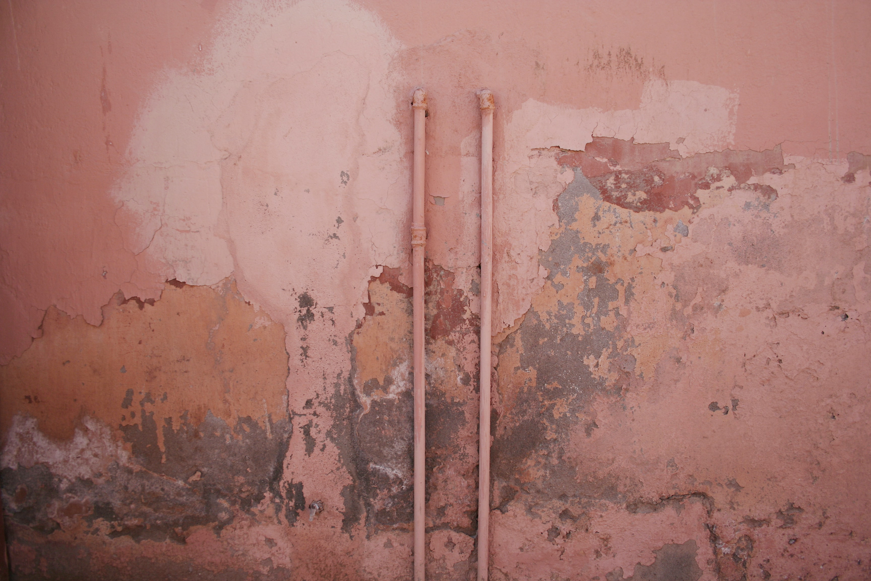 A pink dilapidated wall and pipe in Marrakech