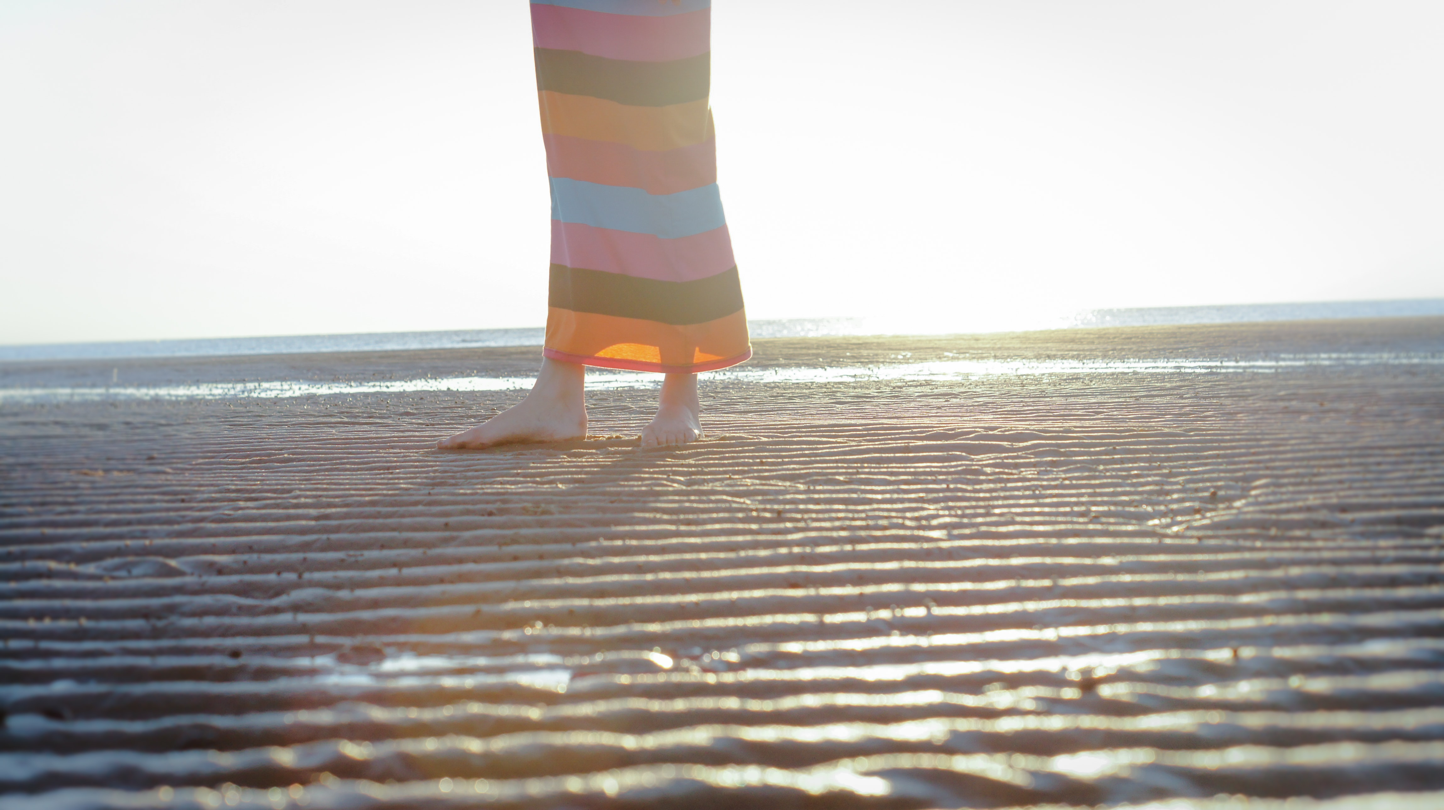 View of woman's legs in a colorfully striped outfit standing on the wet sand beach in Villas