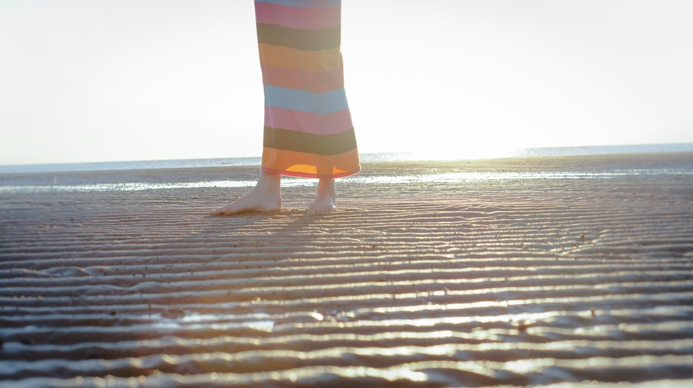 shallow focus photo of person standing on shore