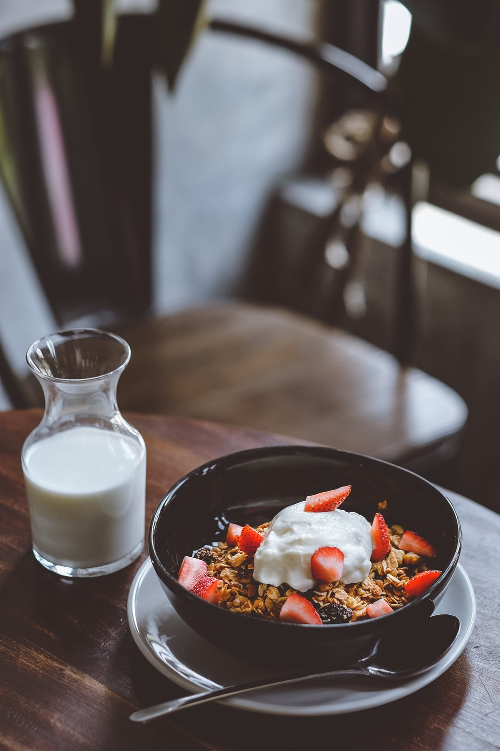 bowl of cereal with strawberries beside glass of milk on table