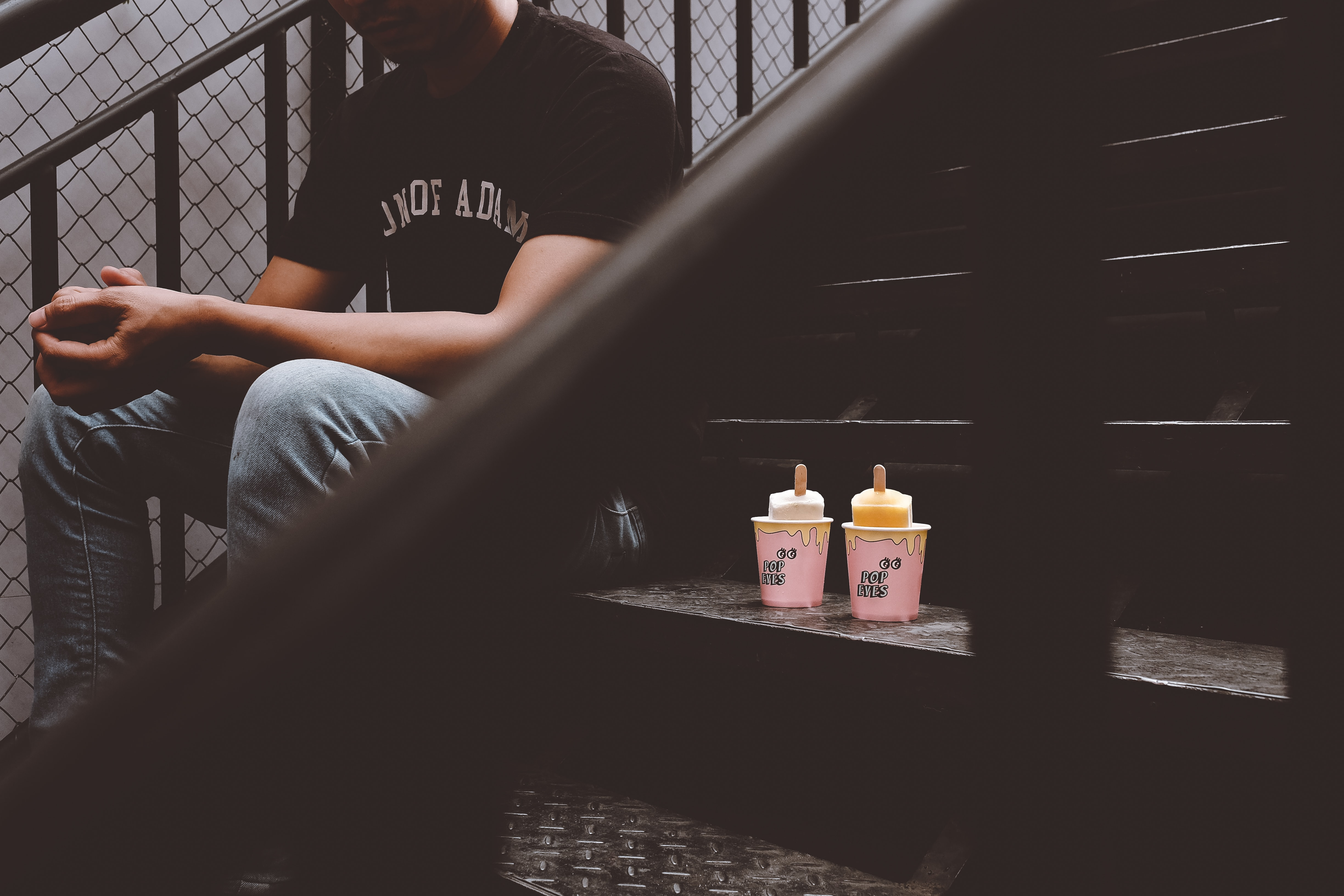person sitting on stair with two disposable cups
