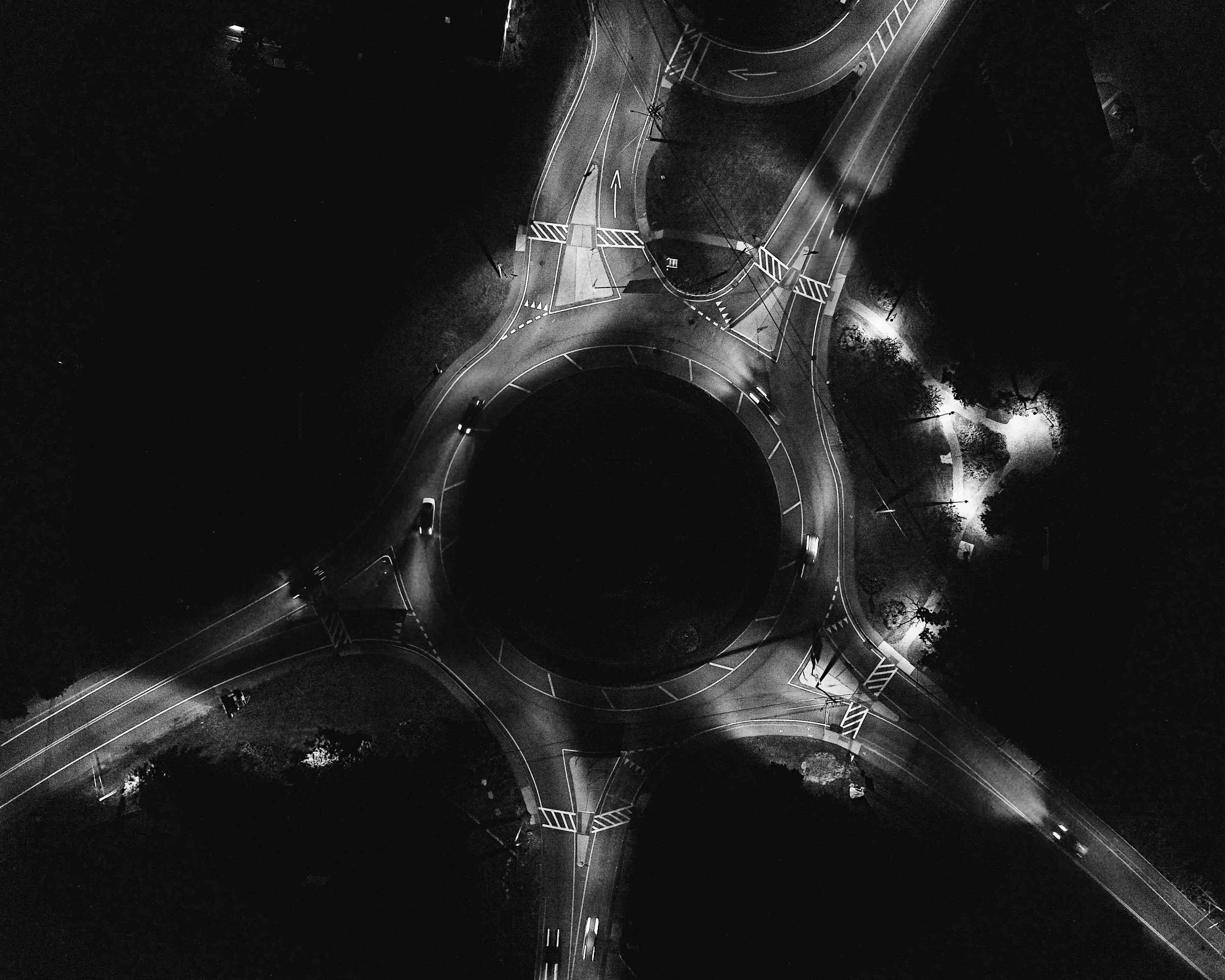 A dim drone shot of a traffic circle illuminated by streetlights