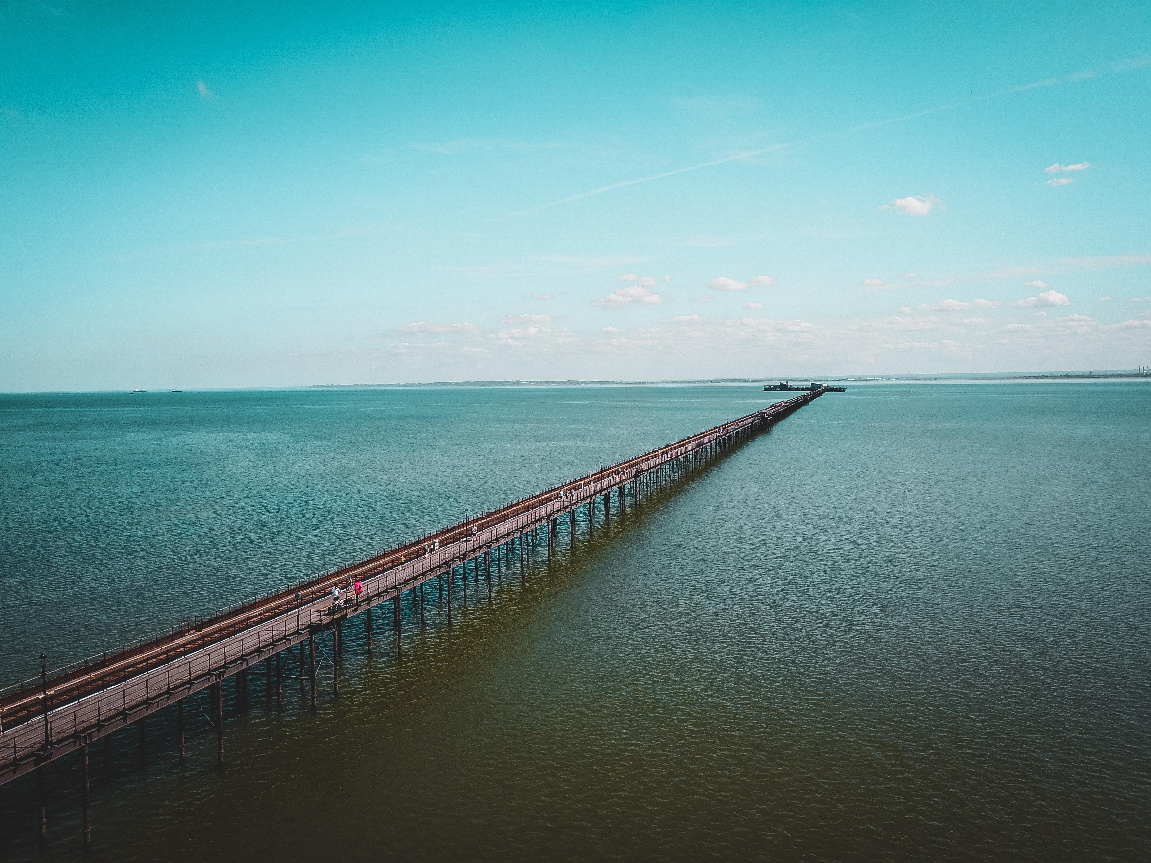 A drone shot of a walking bridge over the bay or ocean