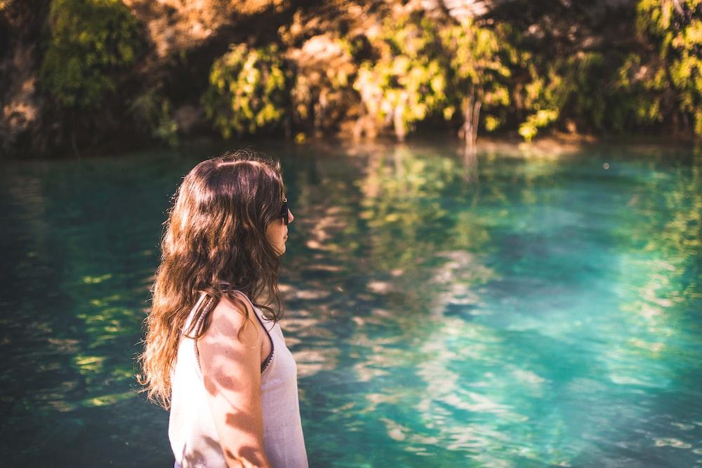 woman wearing white tank top walking beside body of water during daytime