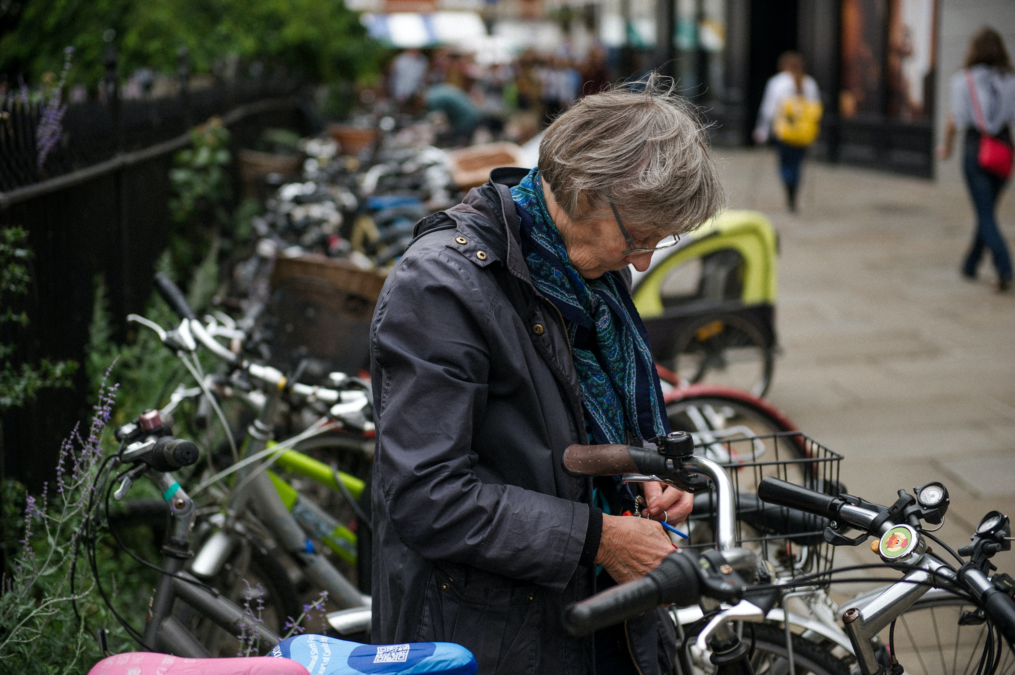 shallow focus photography woman in black zip-up jacket beside gray bicycle near commercial buildings during daytime