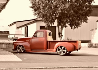 sepia photography of parked classic red single cab pickup truck