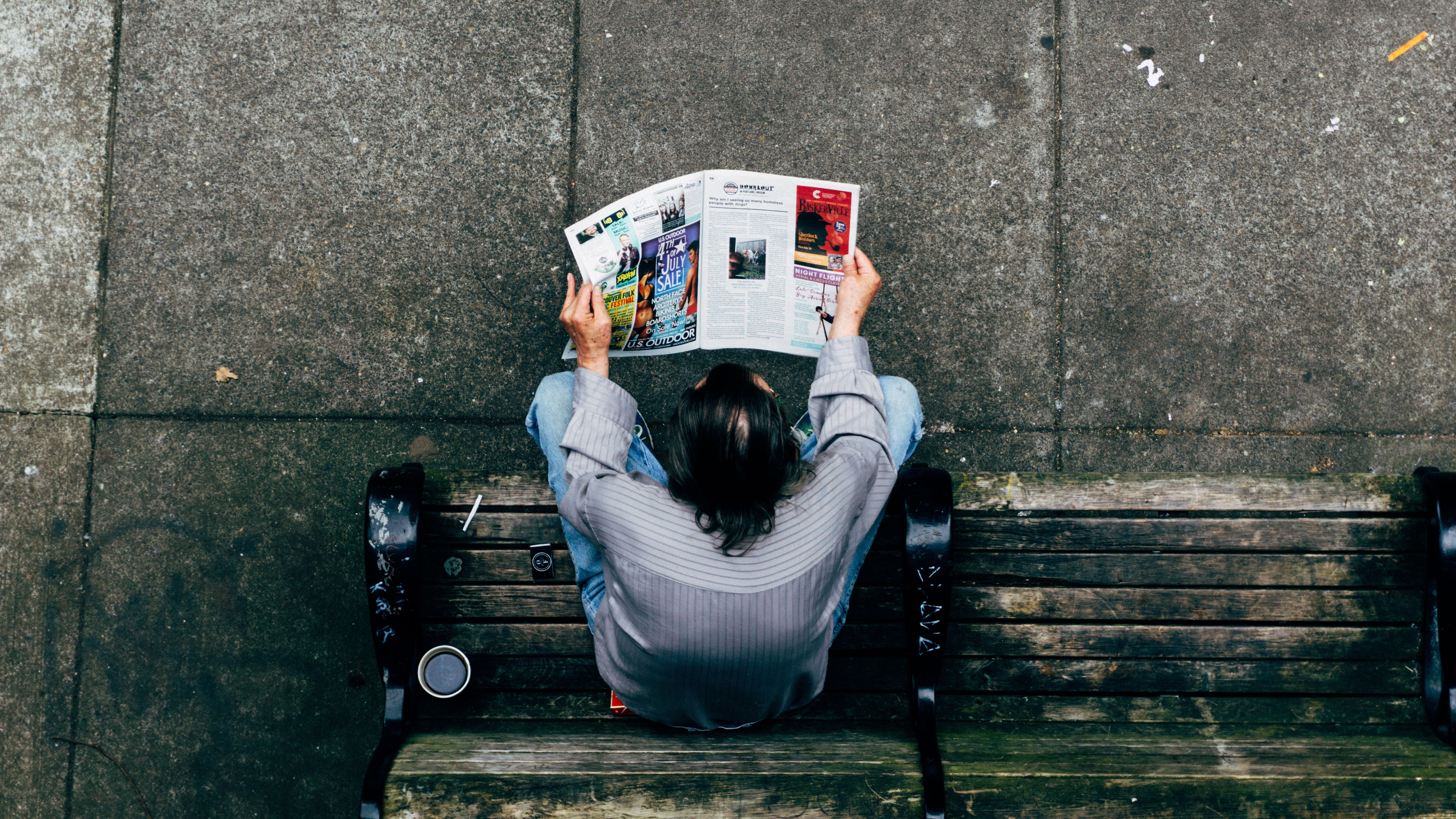 man reading newspaper sitting on bench aerial photography