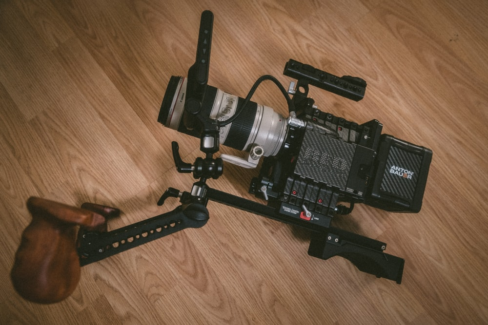 black and gray professional camera on brown wood parquet floor