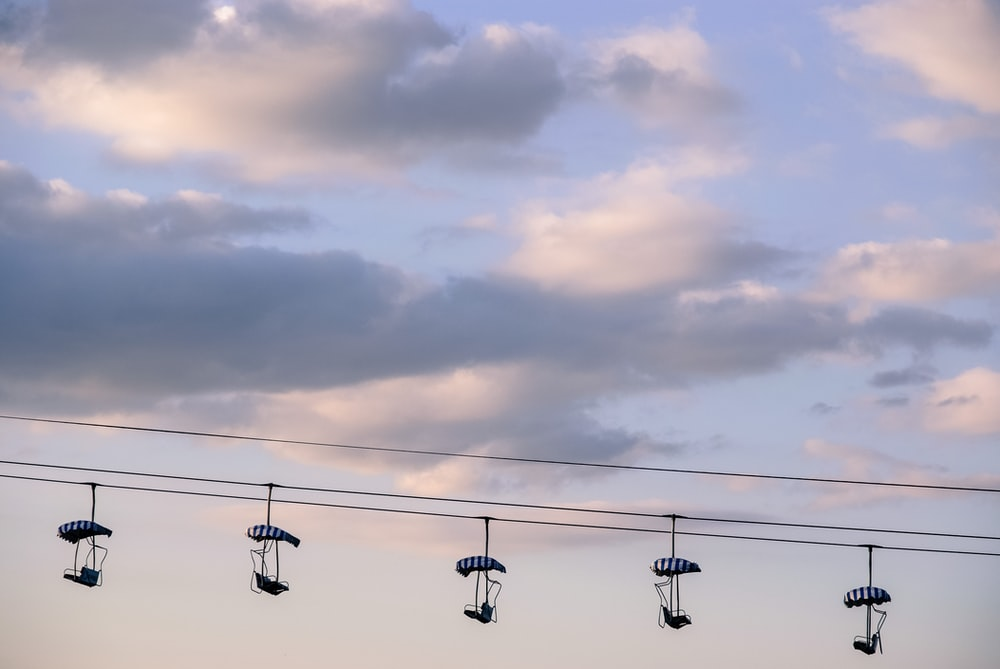 five black cable cars under white cloudy sky