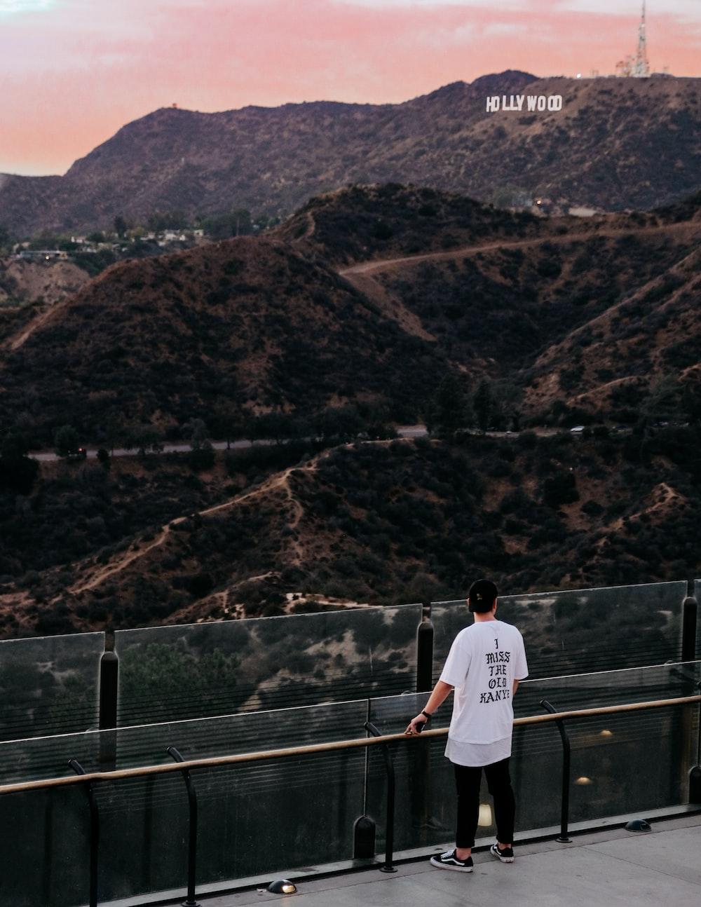 man standing watching mountain during daytime