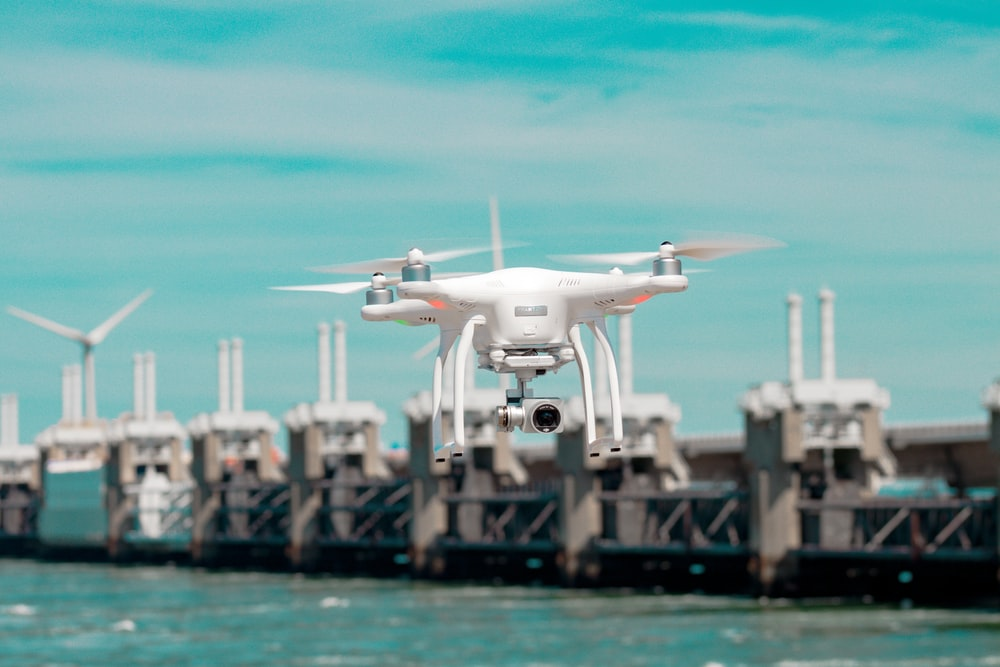 selective focus photography of white drone hovering above body of water
