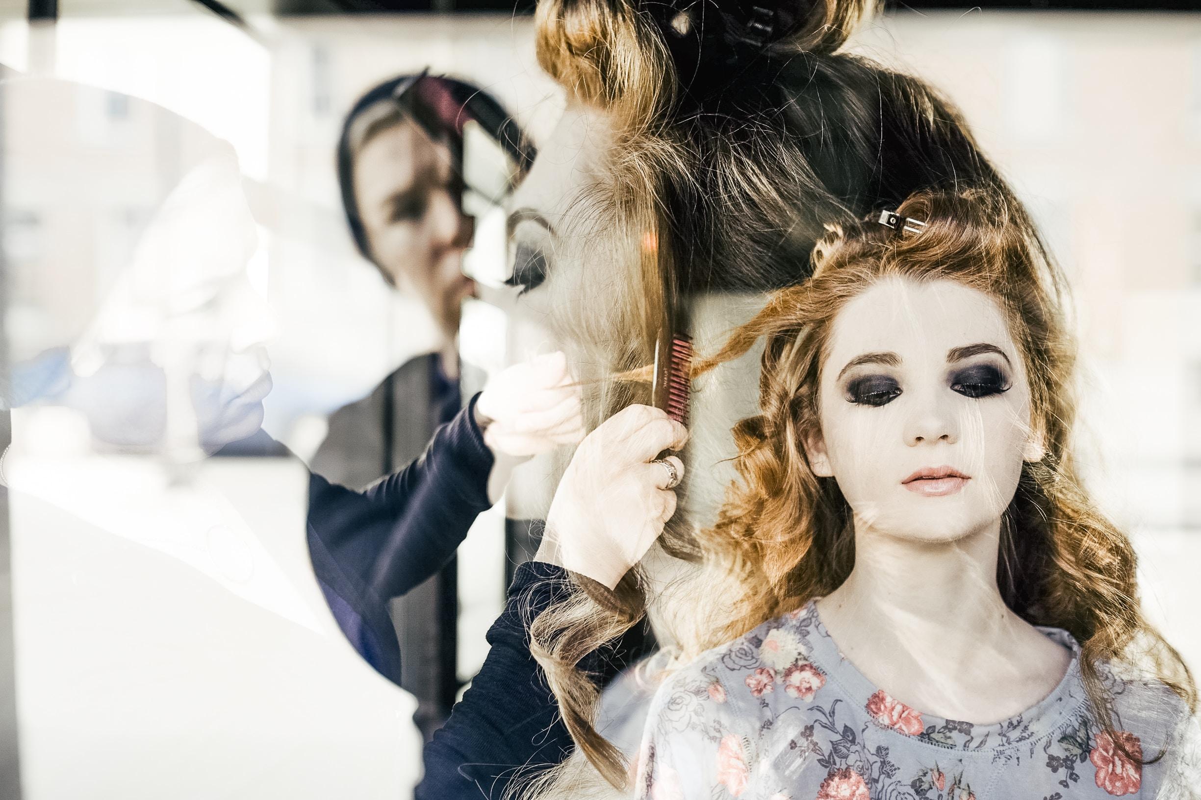 A hairdresser styling a woman's hair seen through a window