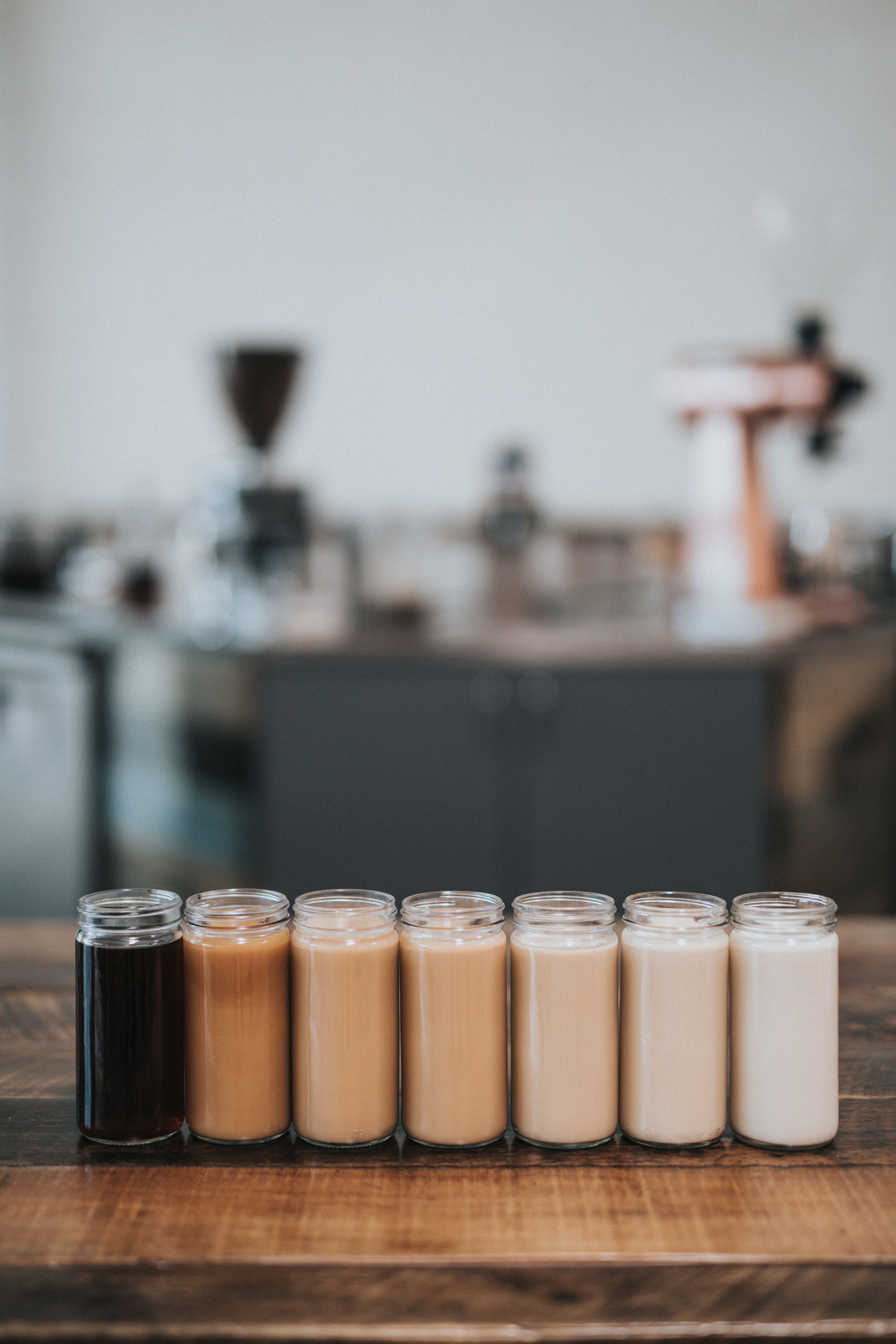 Scented candles in various shades of brown standing in a row on a wooden surface