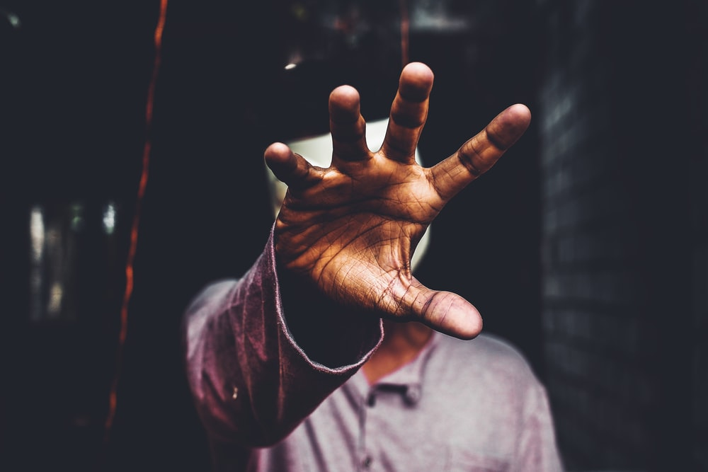 selective focus photography of man raising his right hand during daytime