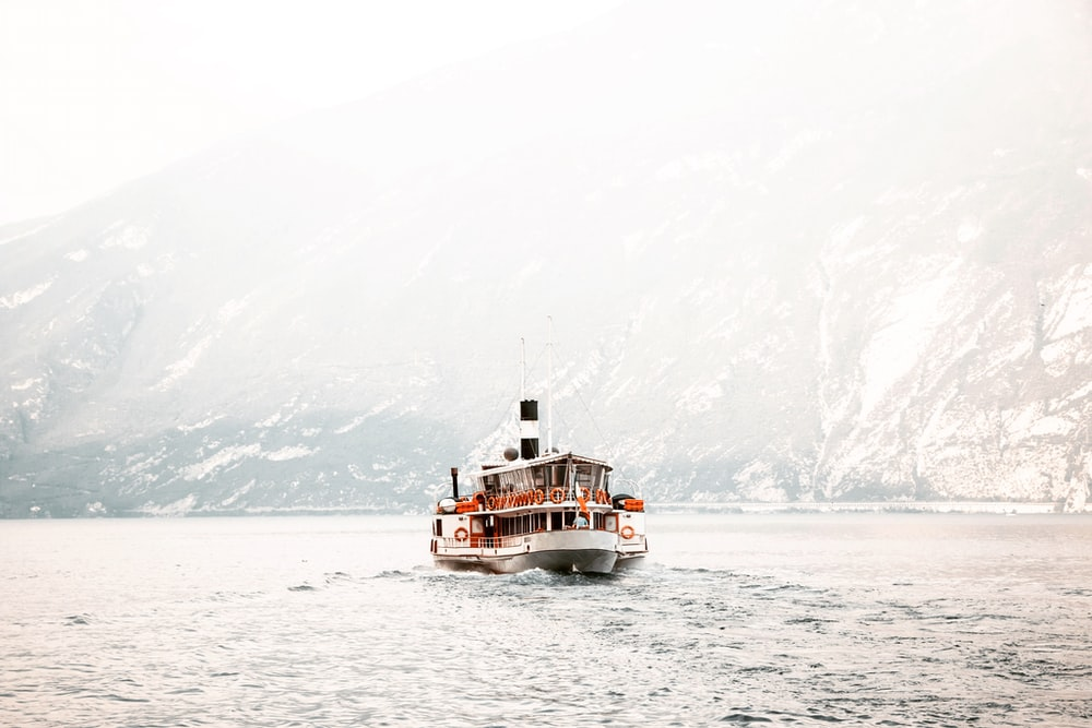 white and black ship on calm body of water near mountain