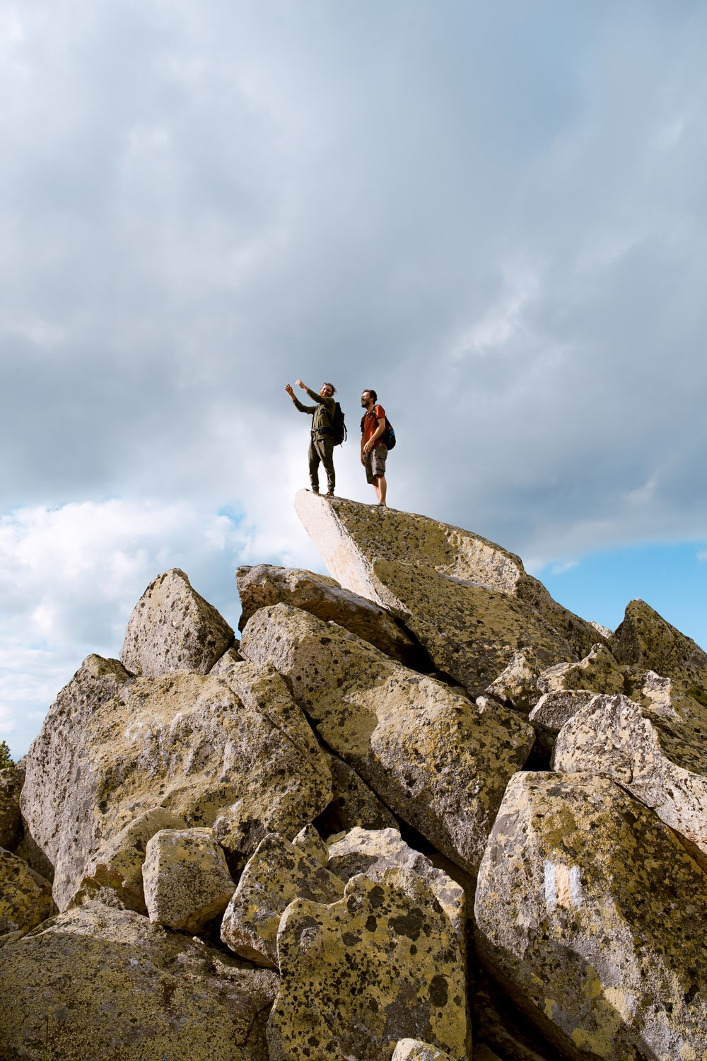 two people standing on grey rock under white clouds