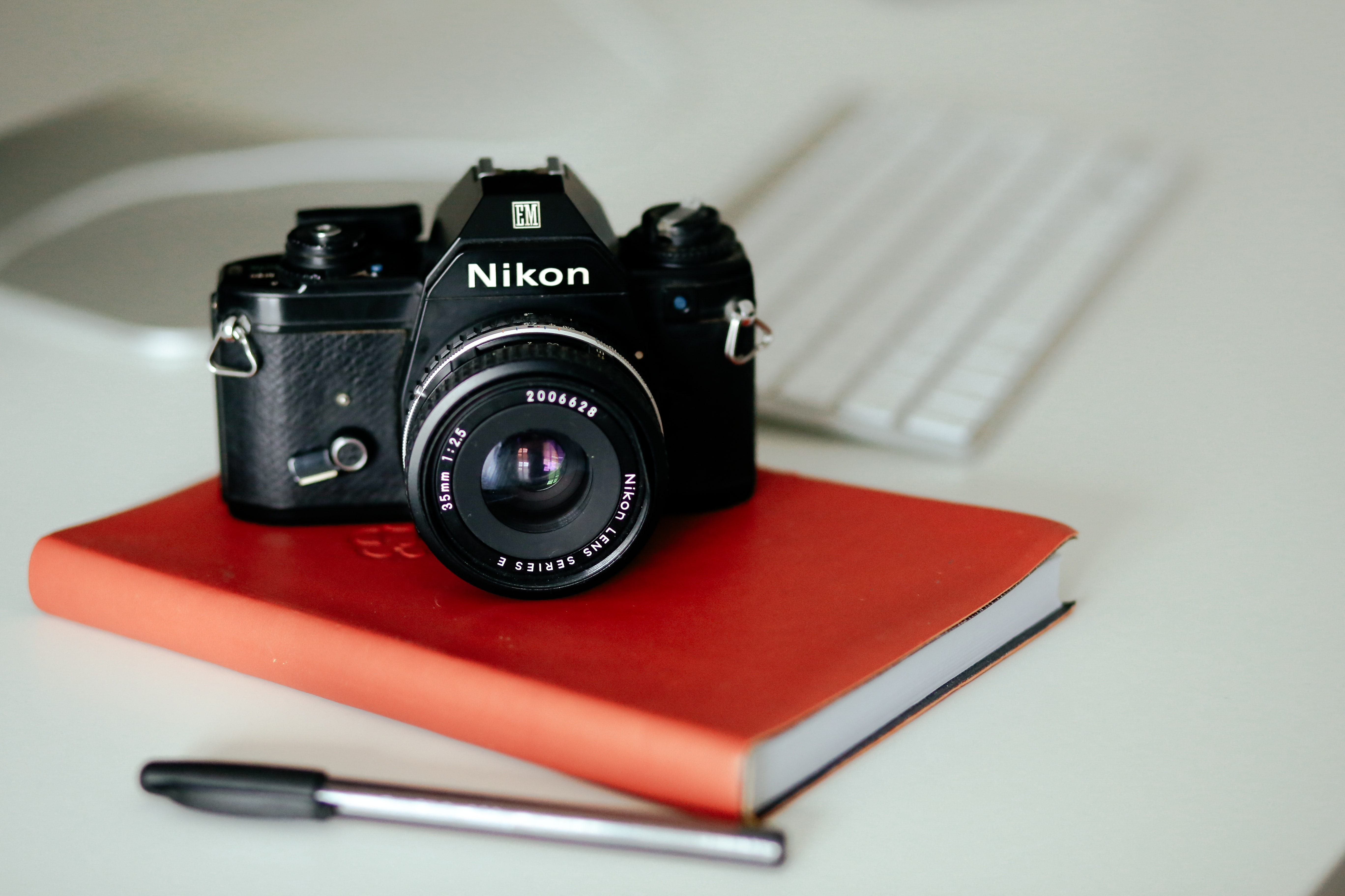 Nikon camera with 35mm lens on a red book beside a black pen and an apple keyboard