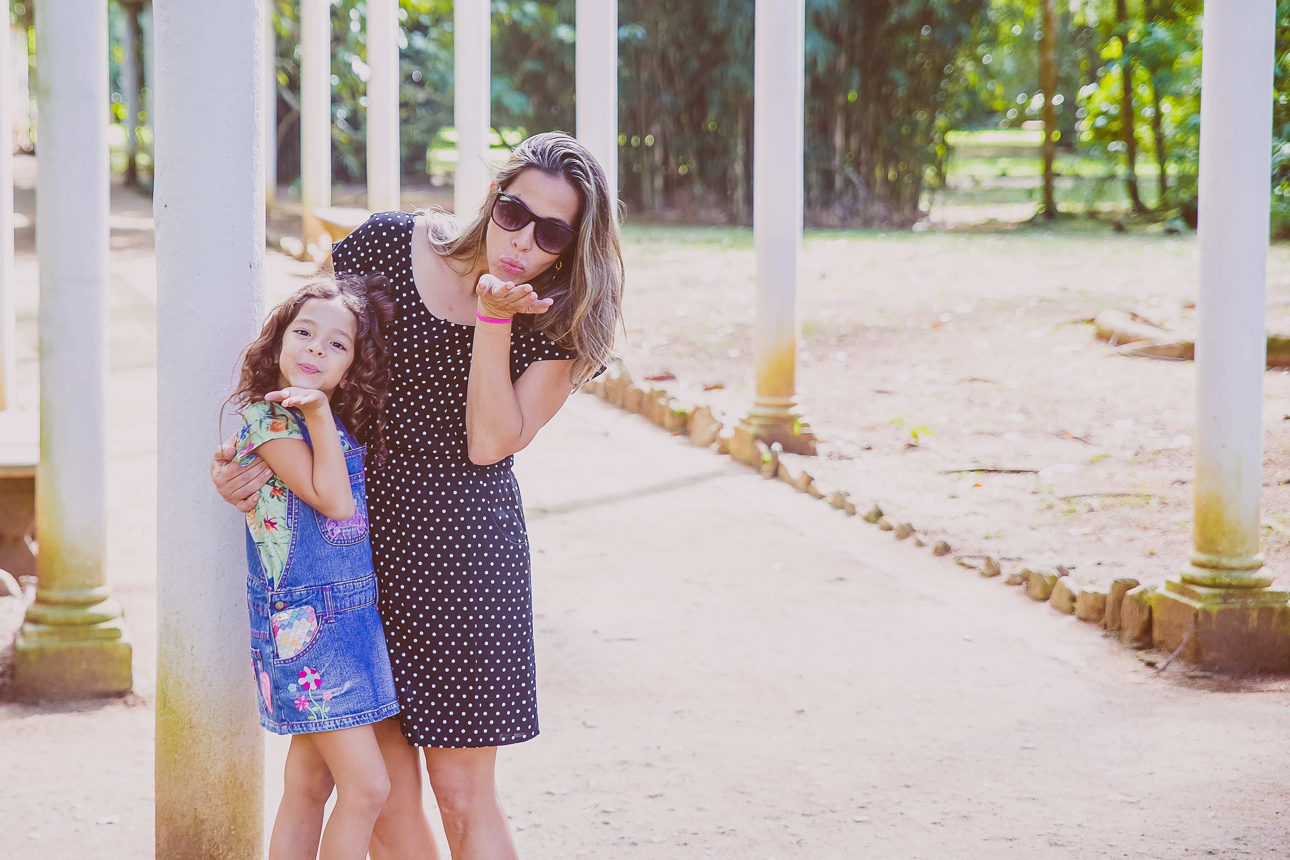 A woman puts her arm around a young girl, and both blow kisses