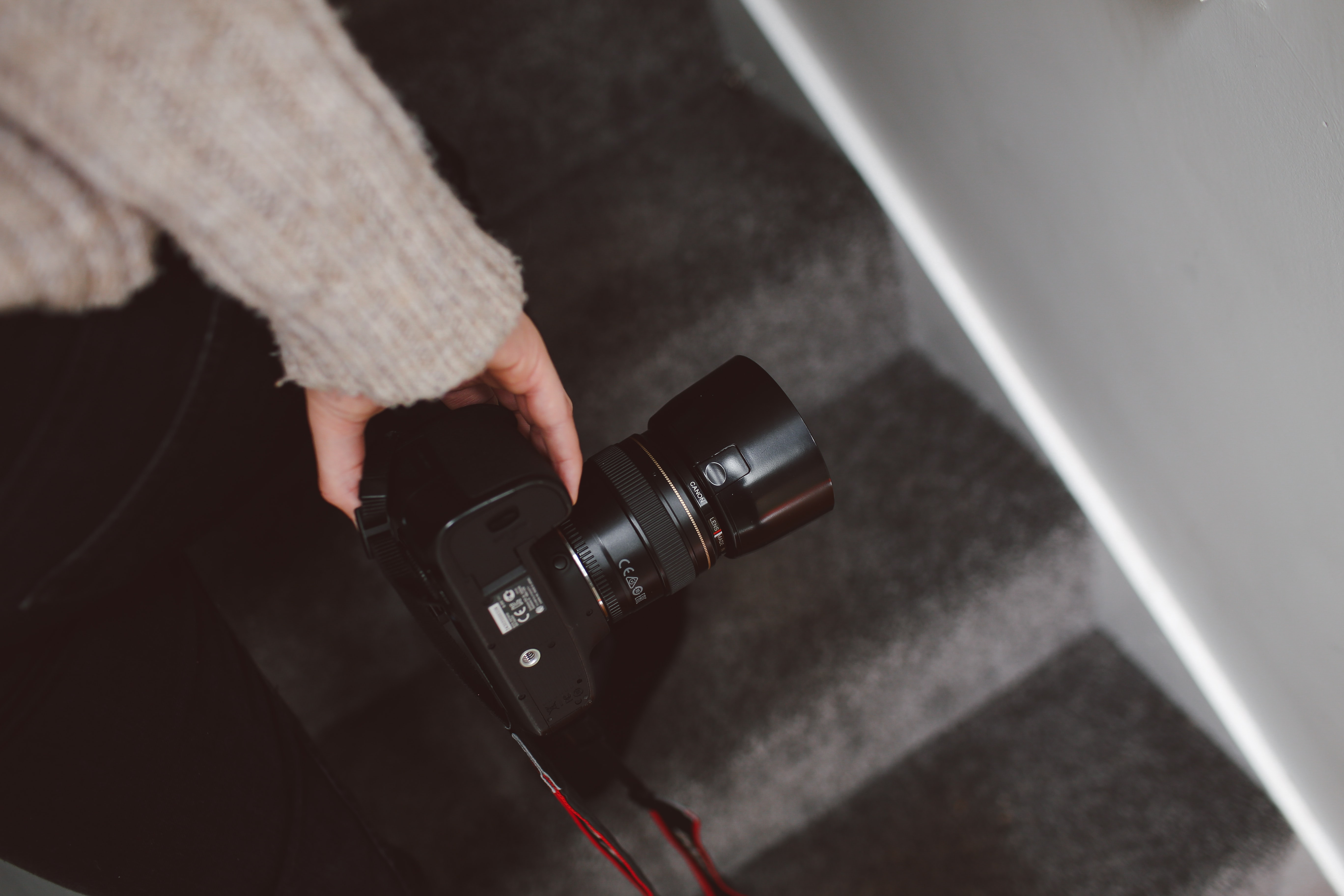A person carrying a long-lens camera while ascending stairs