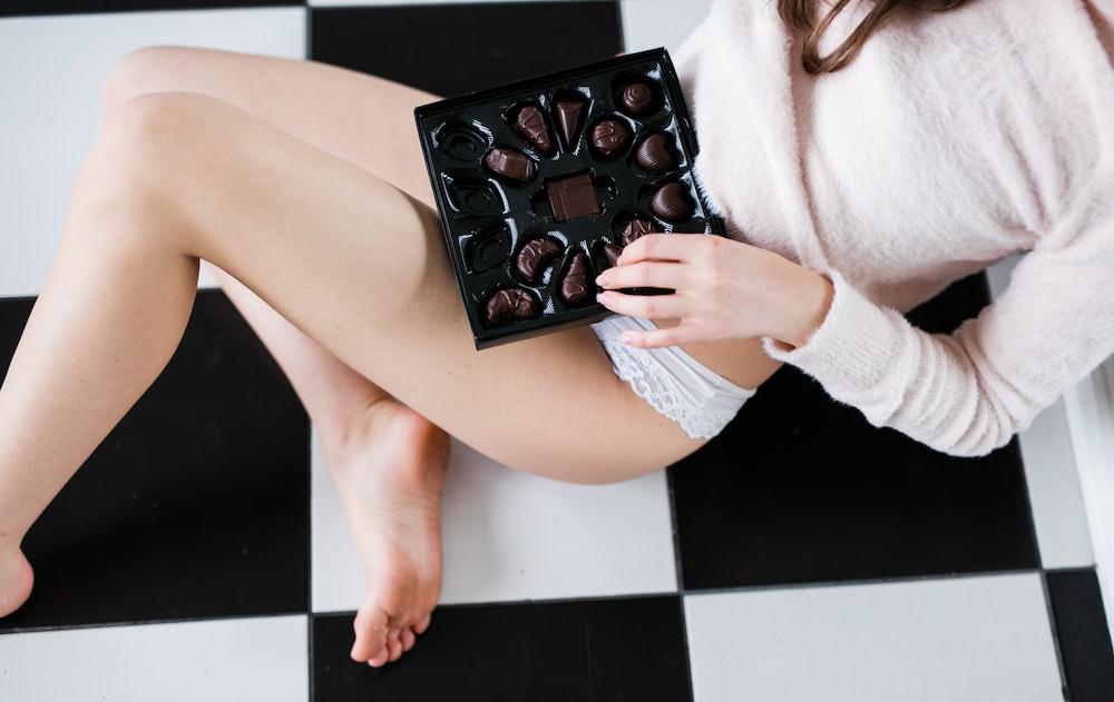 woman wearing white pantie holding chocolate tray