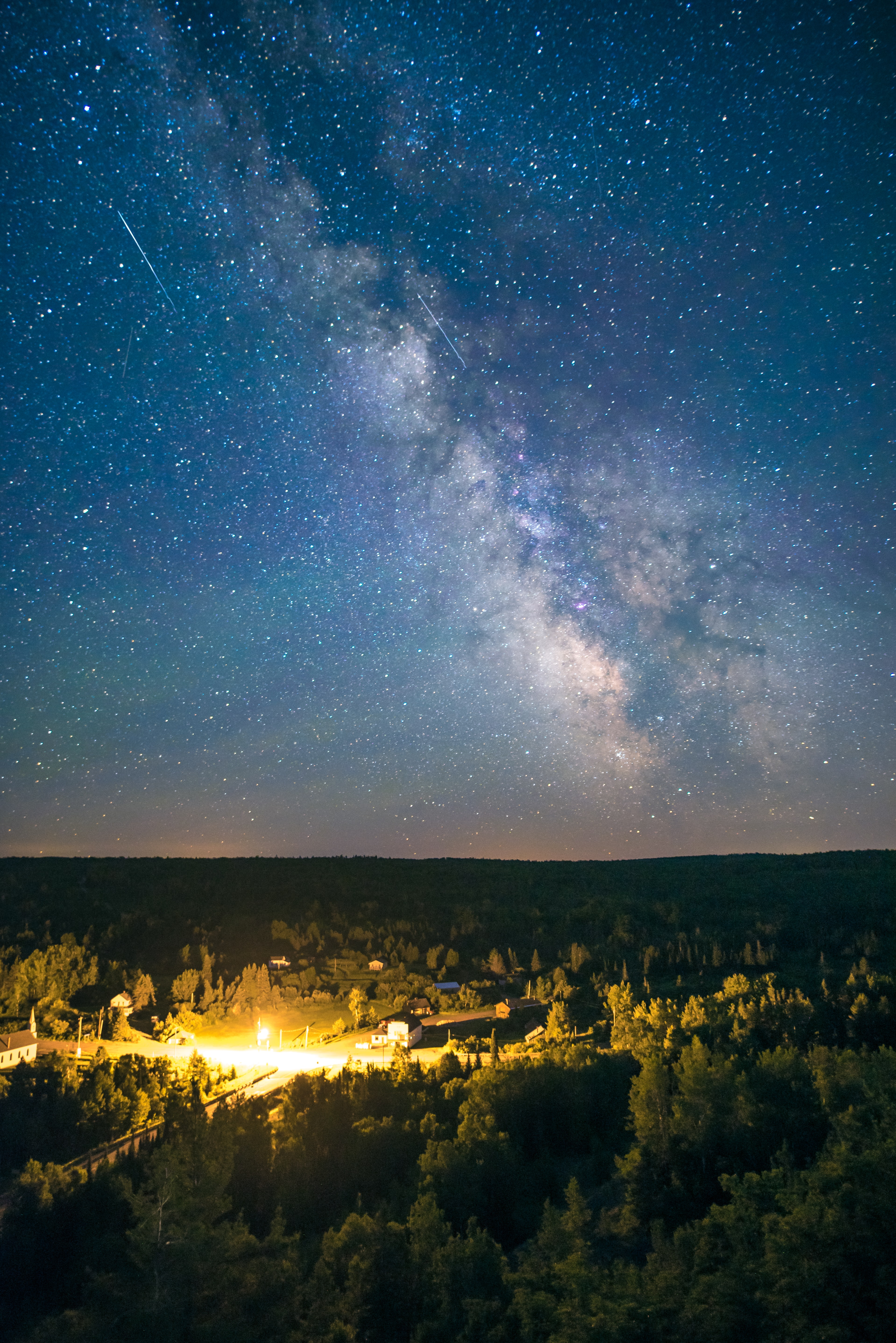 Time lapse of a galaxy over a small town and expansive forest