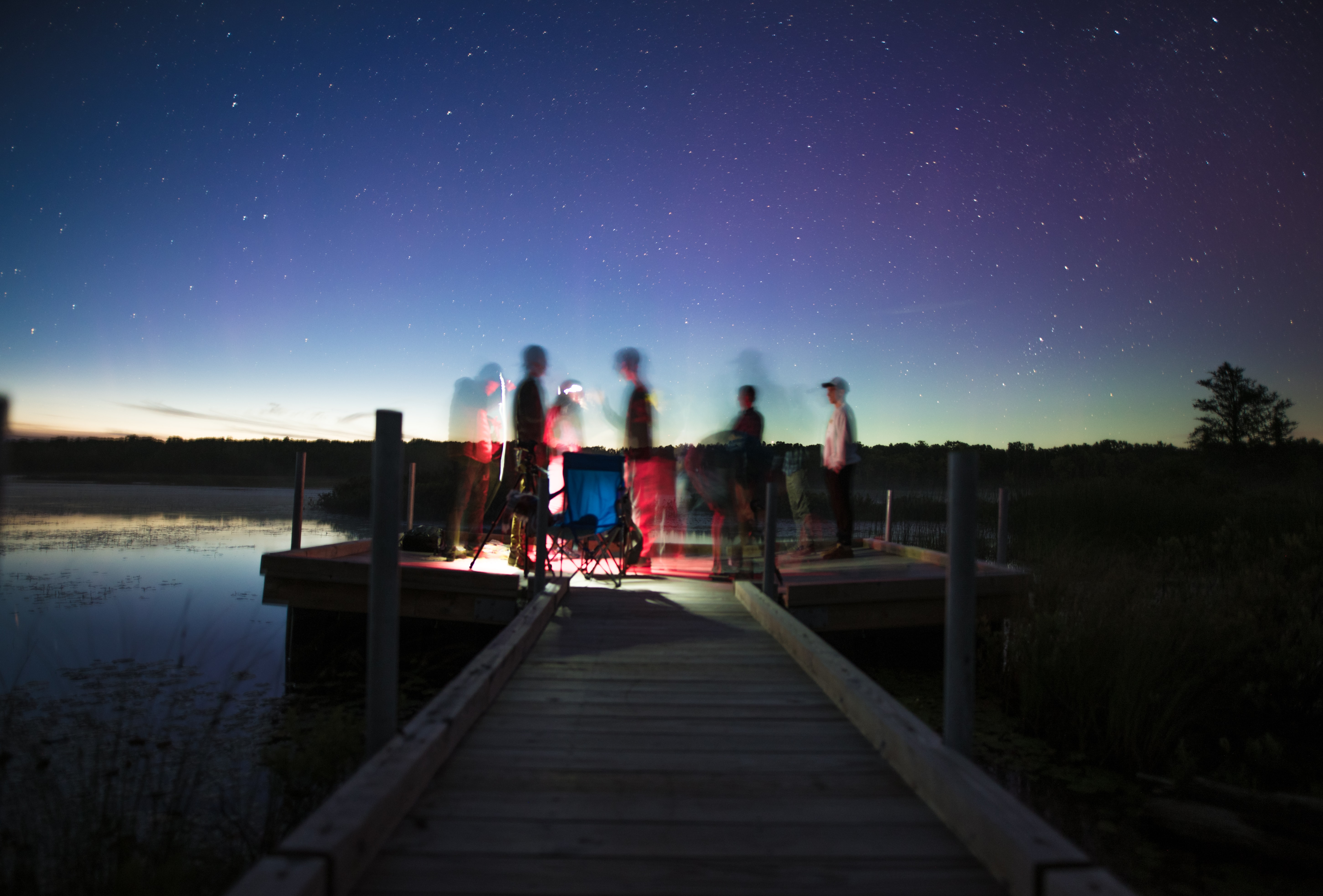 person illustration on brown wooden dock stage photography during nightime