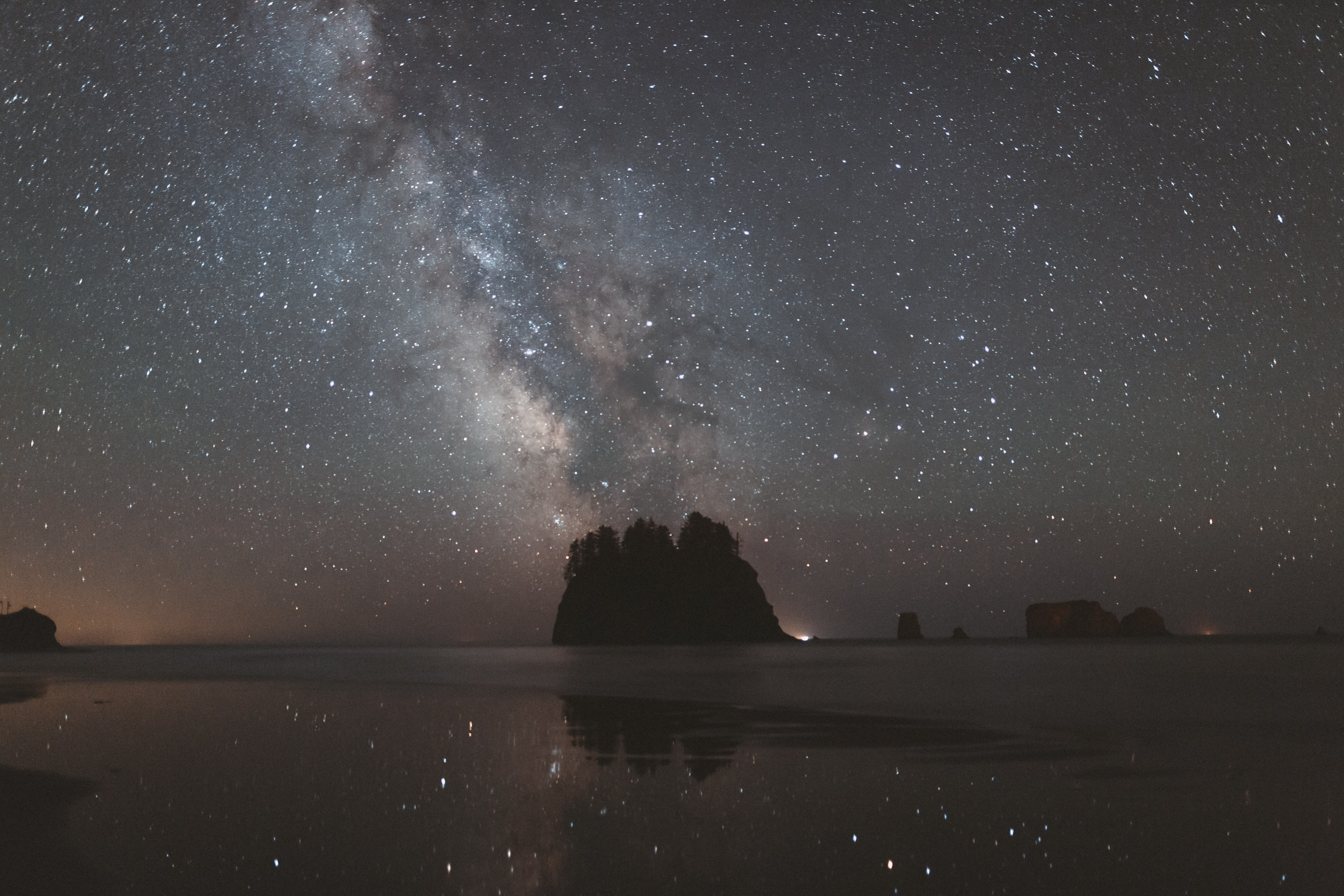 View of the night sky filled with stars and galaxies reflected in the water at Second Beach