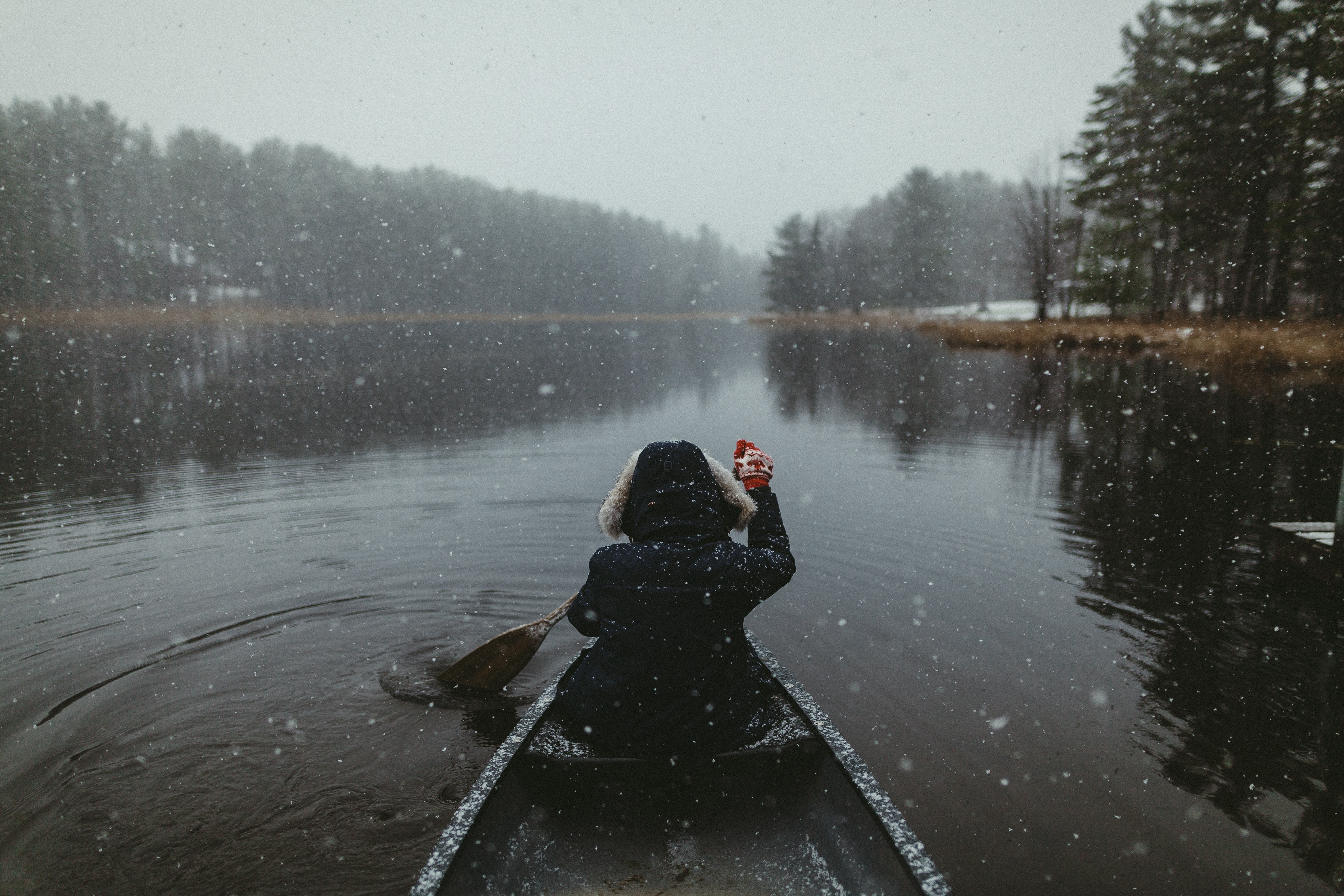 A woman wearing a jacket with a fur hood rowing her canoe through the waters at the Adirondack Mountains