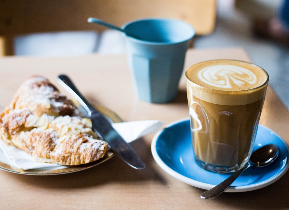 clear glass cup with coffee and spoon on plate near baked bread with bread knife