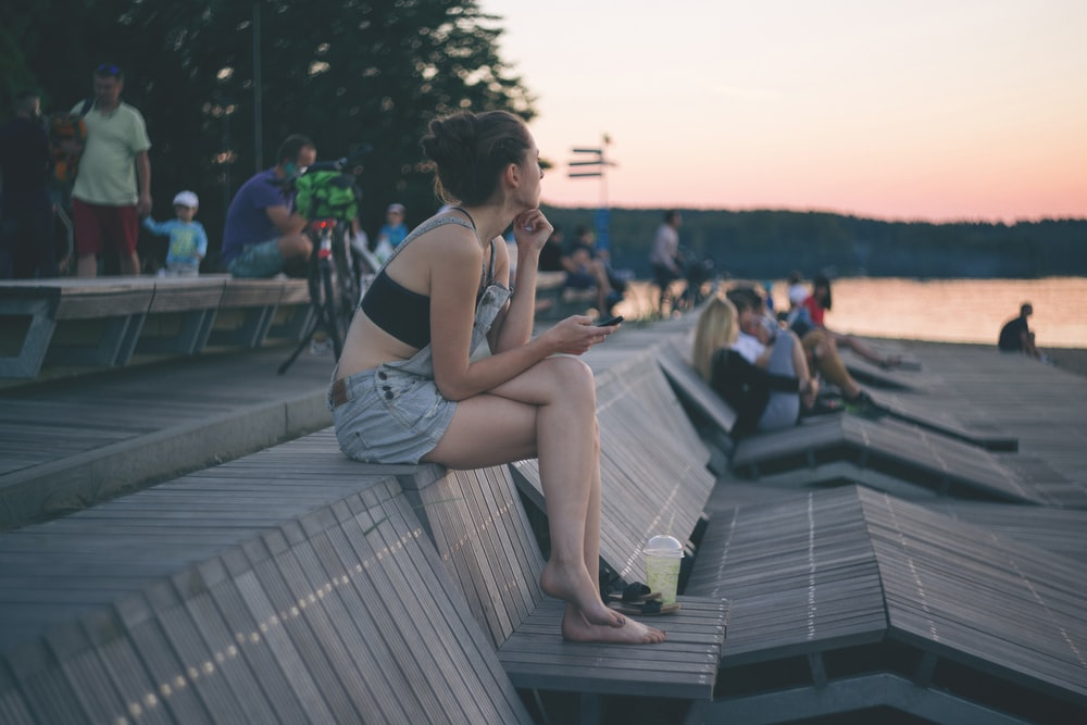 woman sitting on top of wooden bench near people and beach