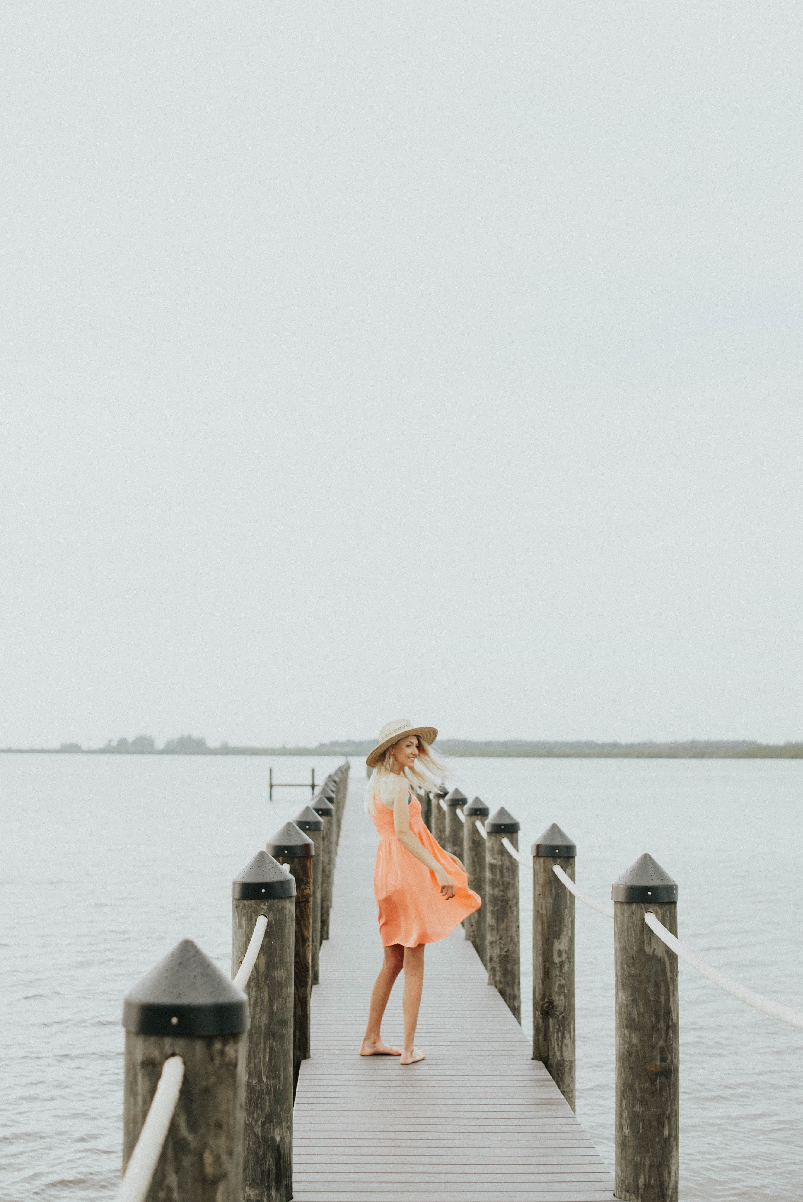 A smiling young woman in a hat and a dress on a wooden pier