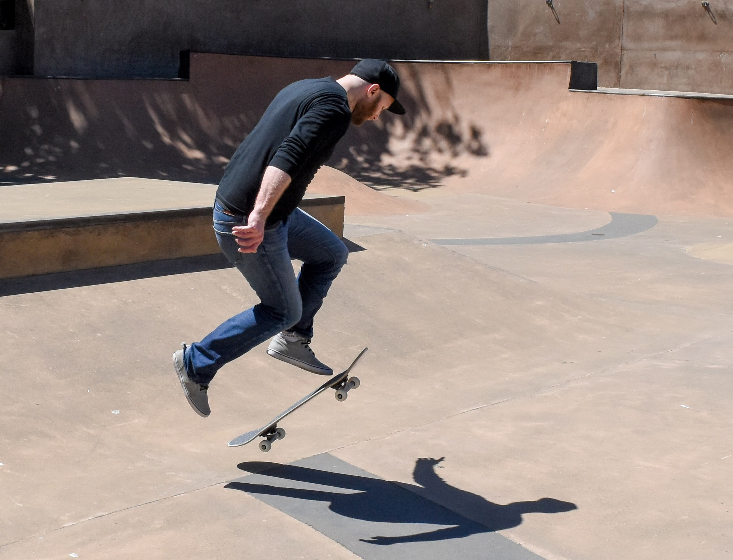 man playing with his skateboard on play yard during daytime