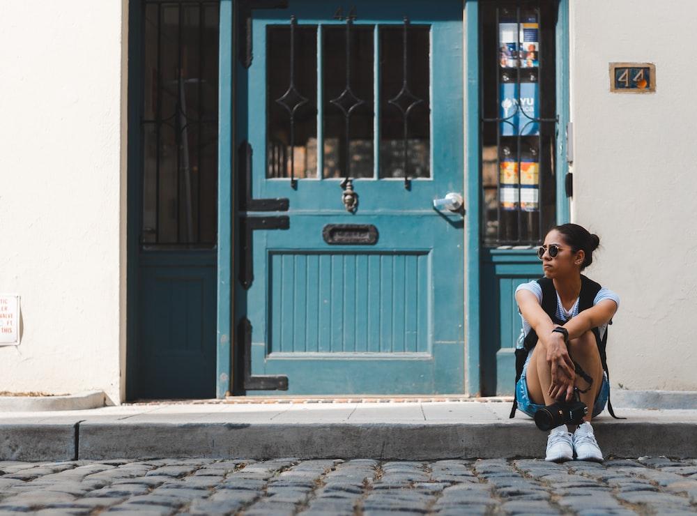 woman sitting near blue door