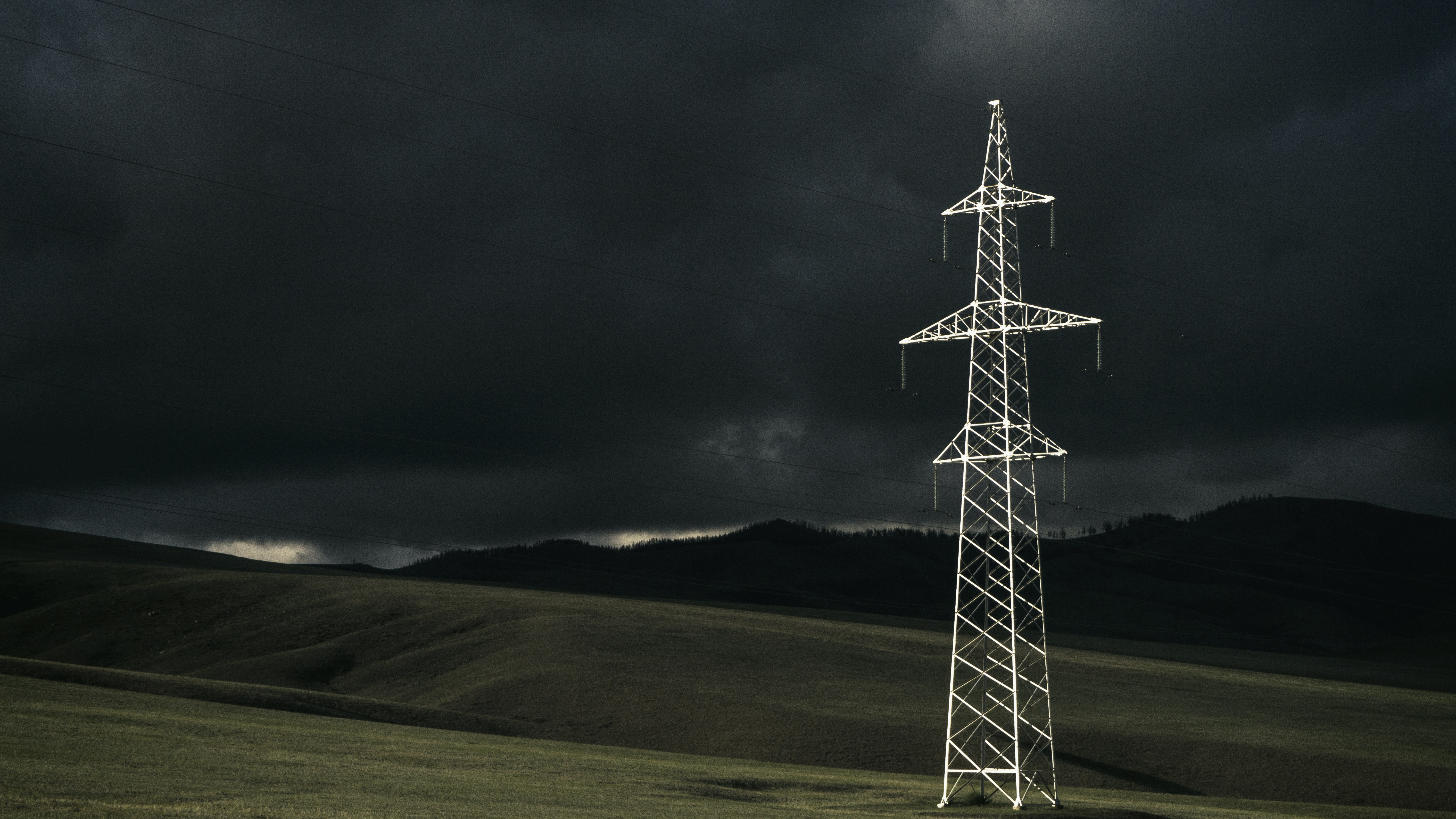 Electrical tower in a farm field on a stormy dark day