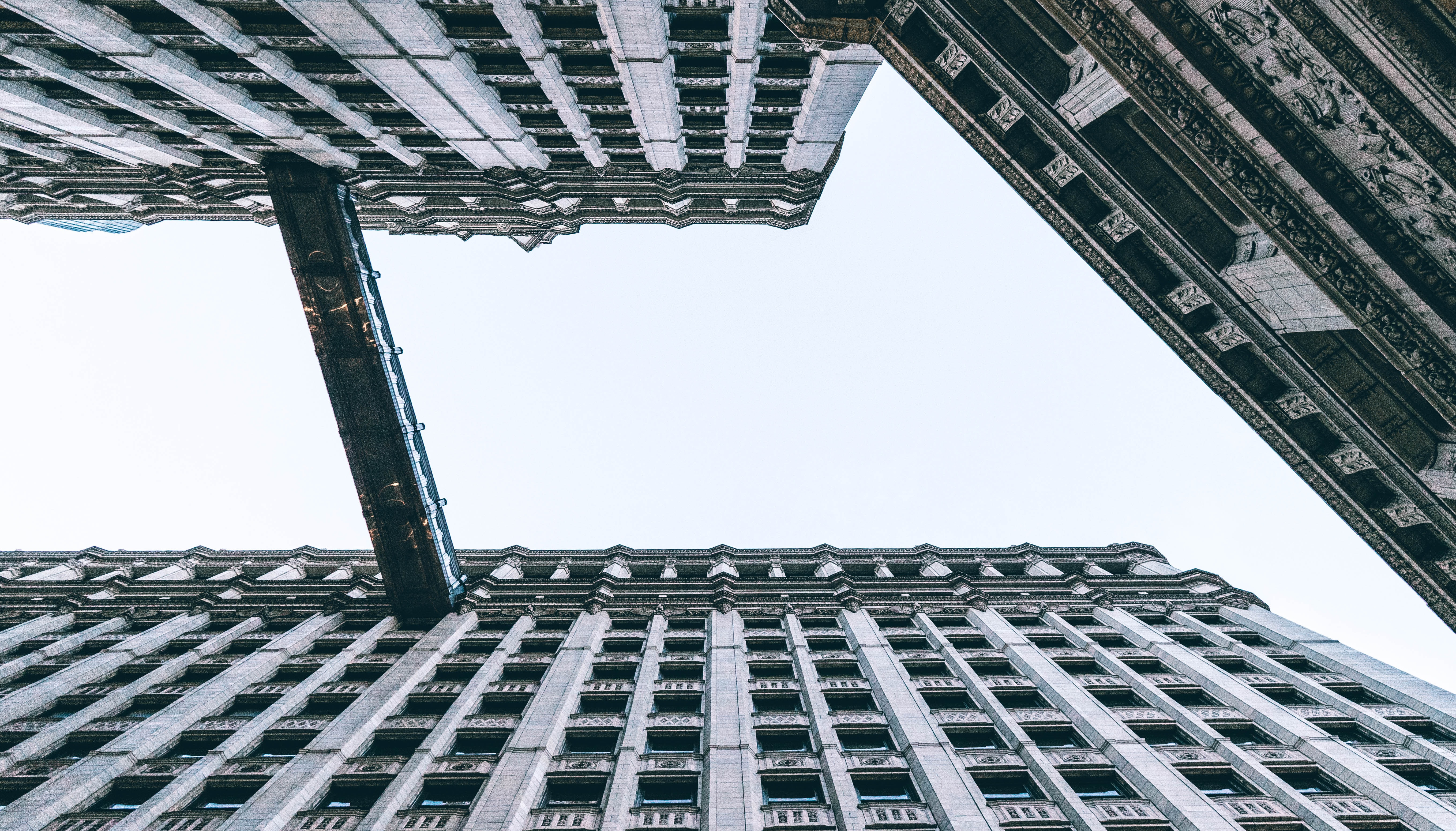 A low-angle shot of a two tall buildings connected with a bridge