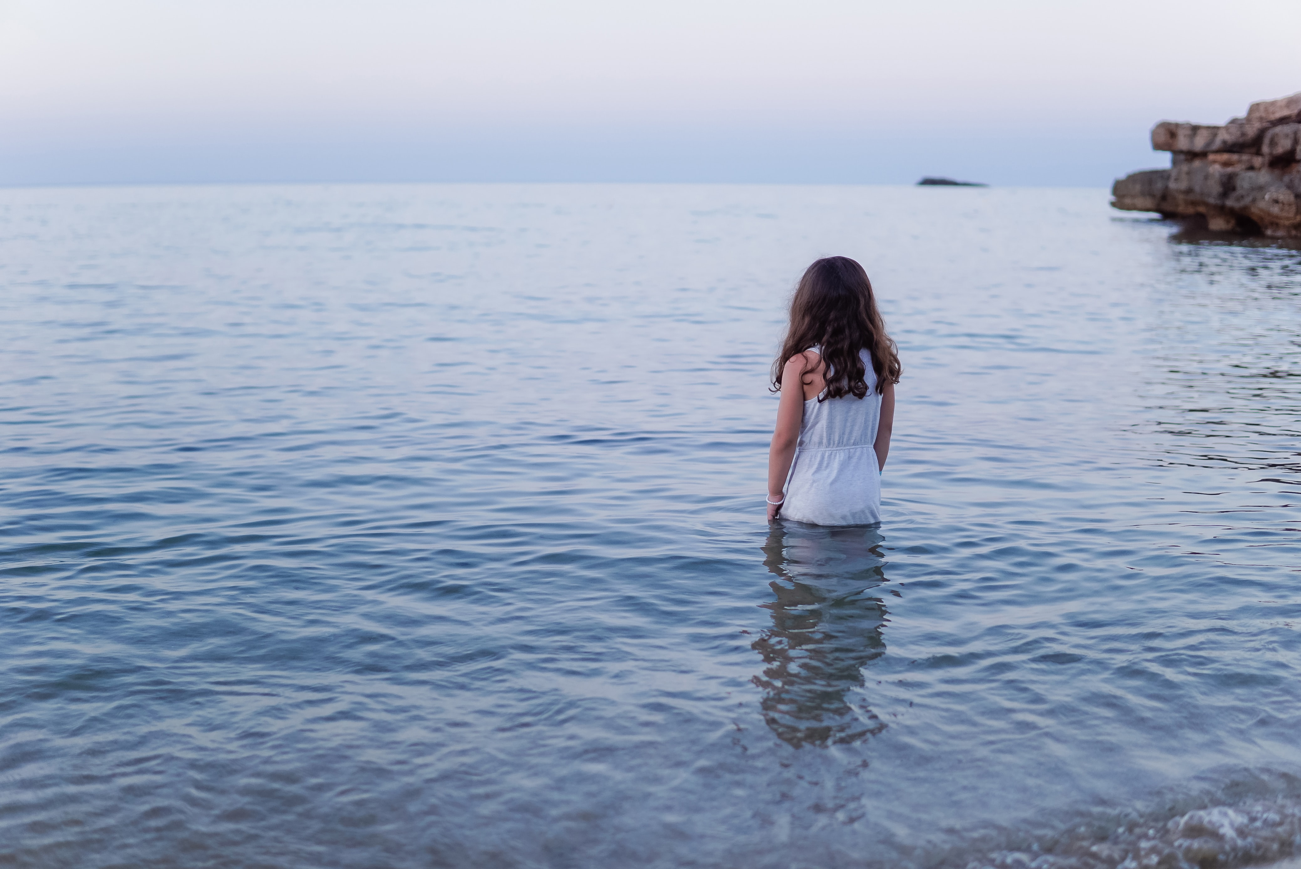 Woman in white dress standing by the waist in the ocean in Es Figueral