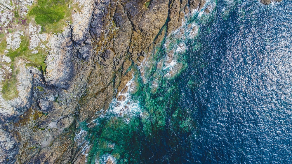 aerial photography of rocky shore near grass covered mountain