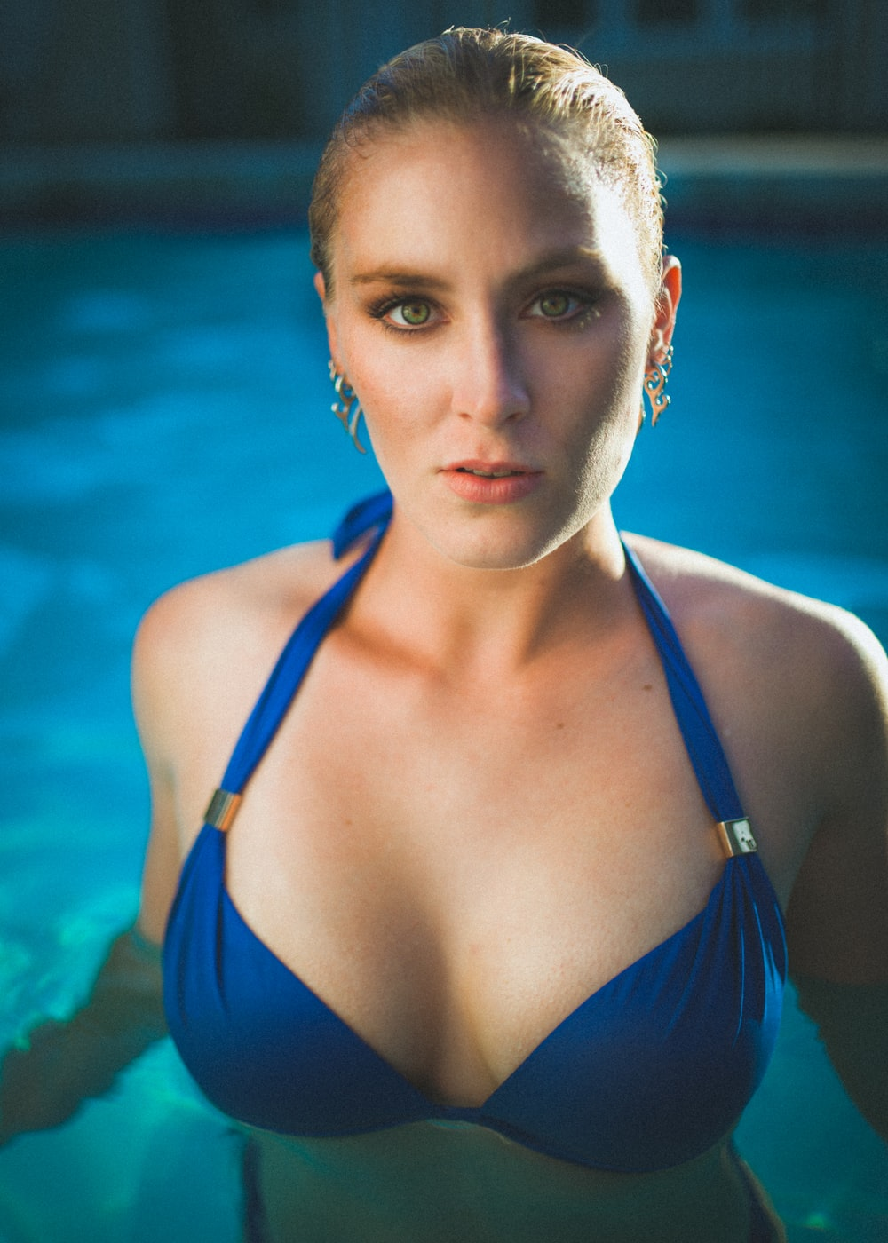 woman in blue string bikini top in pool looking straight