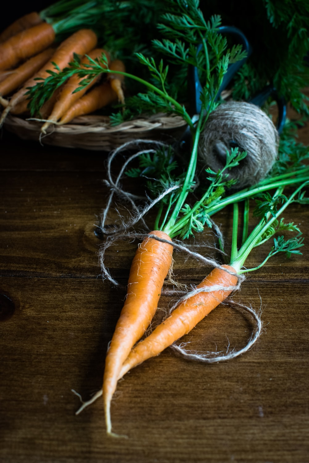shallow focus photo of carrots on brown wooden surface