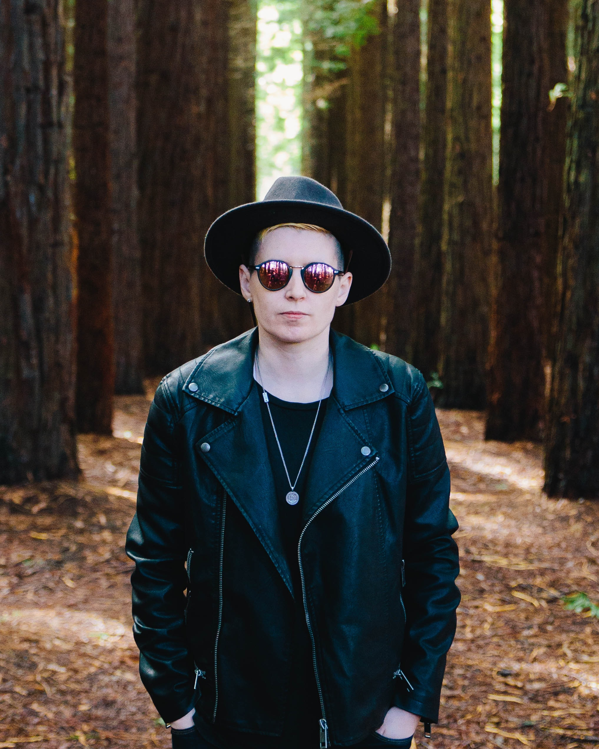 A man in a leather jacket, sunglasses and a hat in a forest