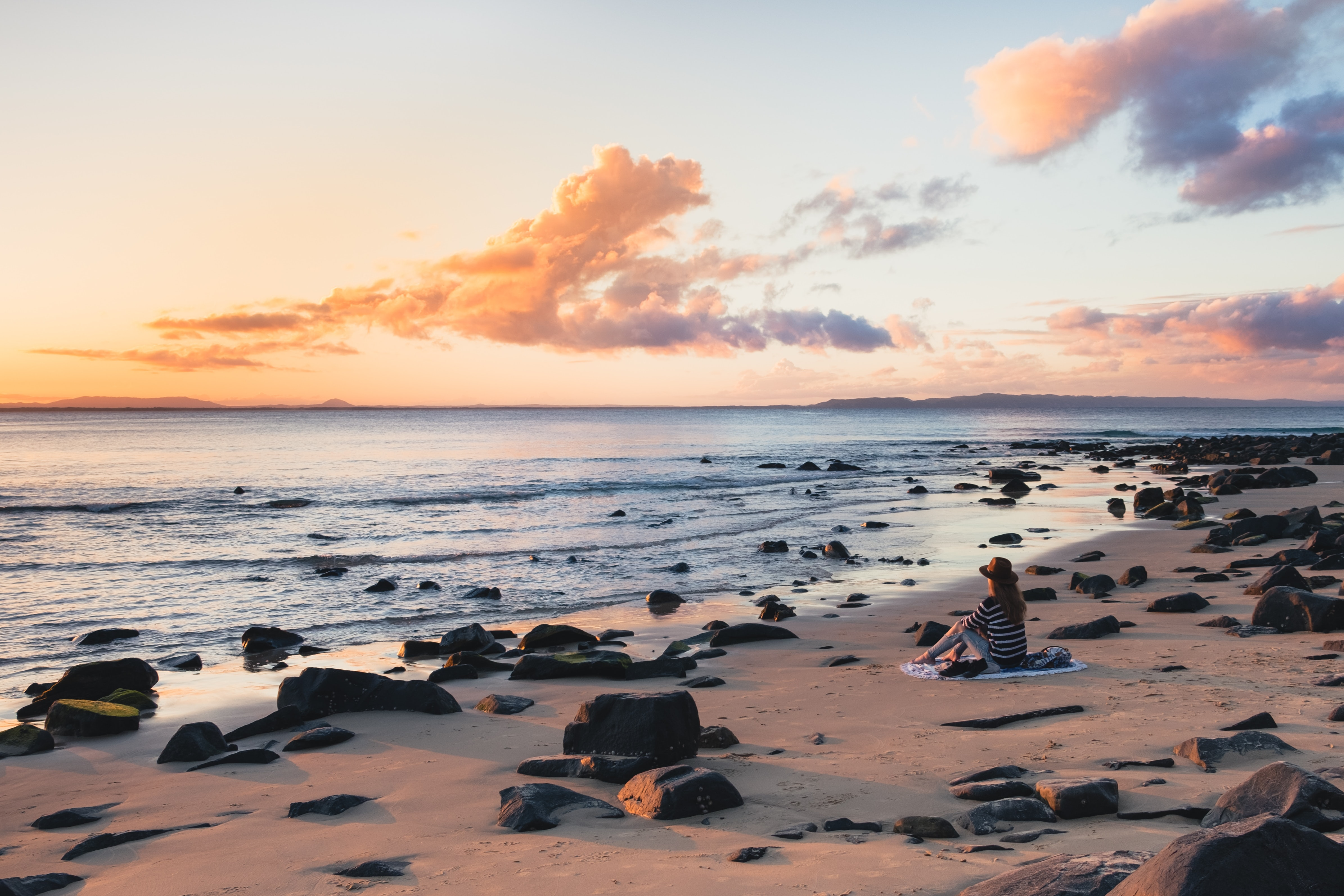 Woman with hat sitting on a rocky sand beach looking at the sunset in Noosa Heads