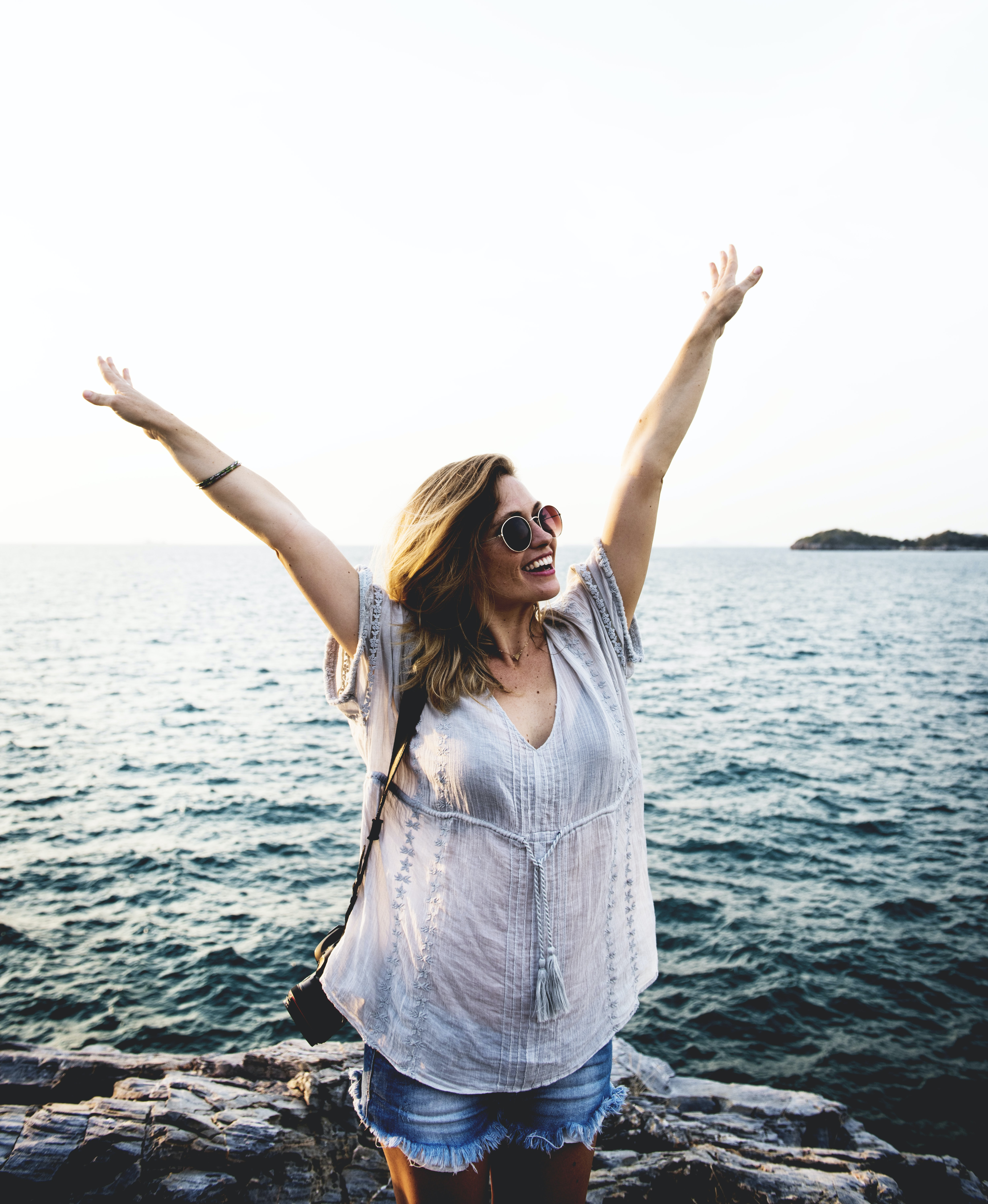 smiling woman raising both arms behind body of water