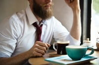 man wearing white dress shirt sitting on chair with coffee on table