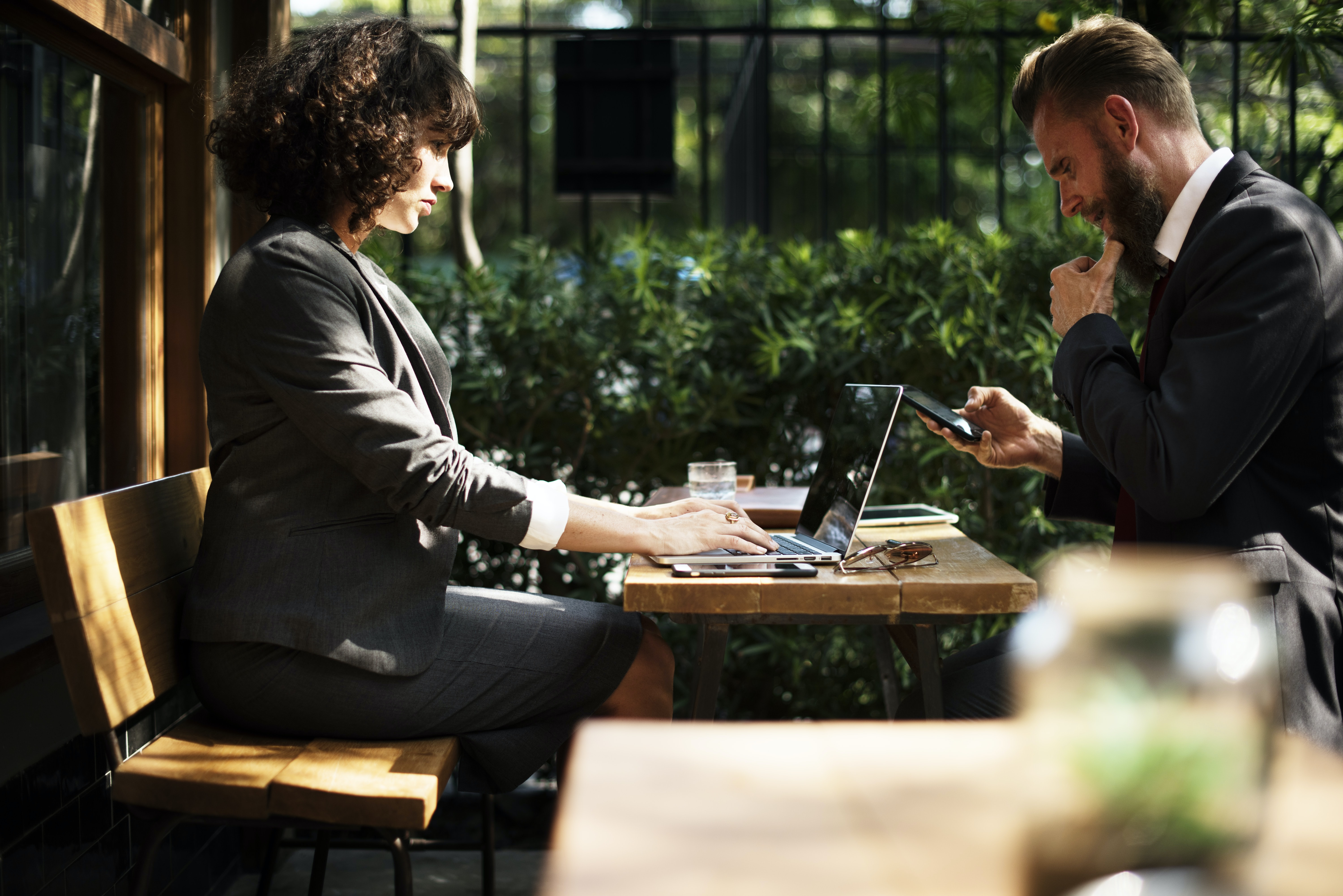 Two people in business attire sitting at an outdoor table with electronic devices
