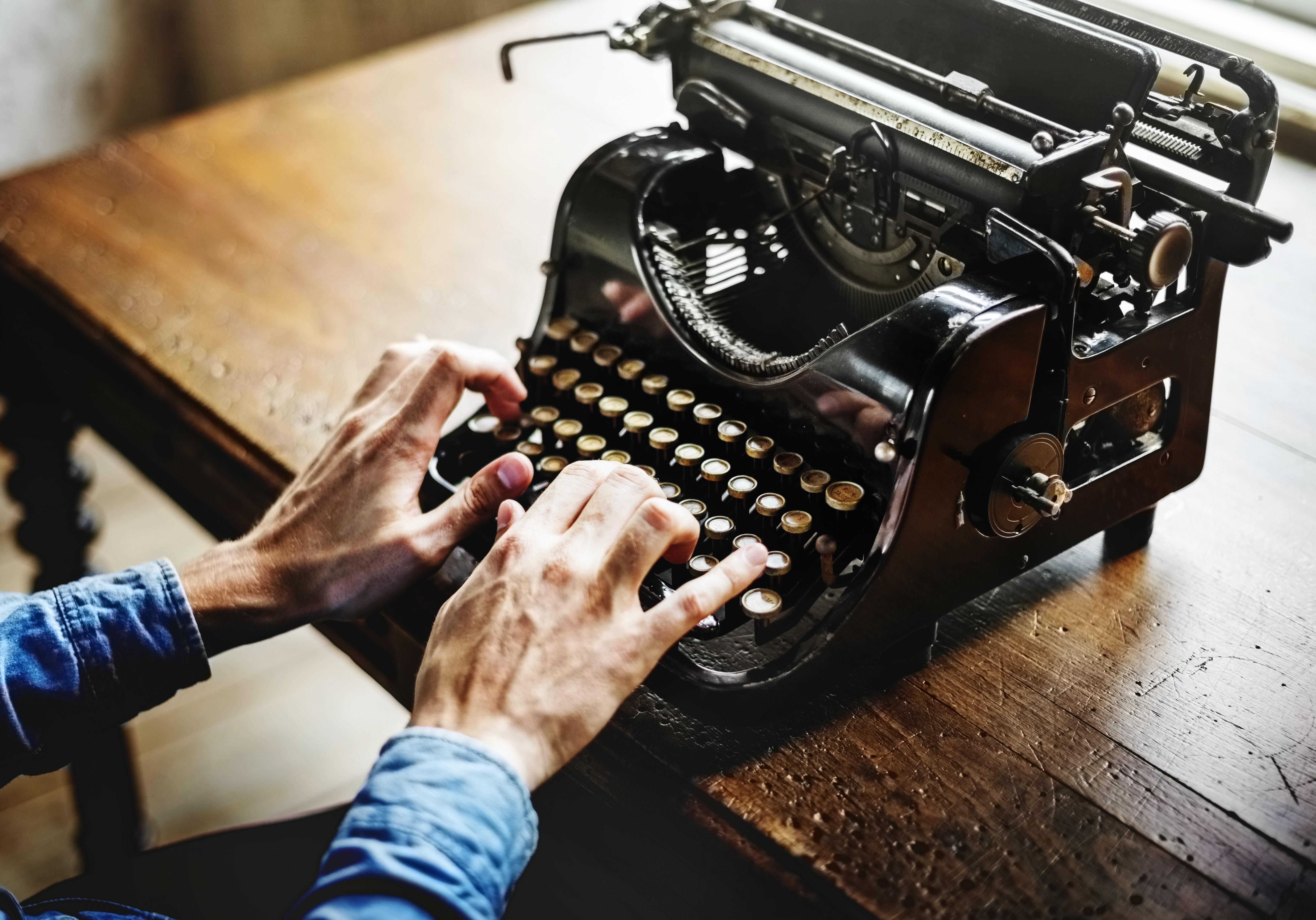 person typing on black typewriter
